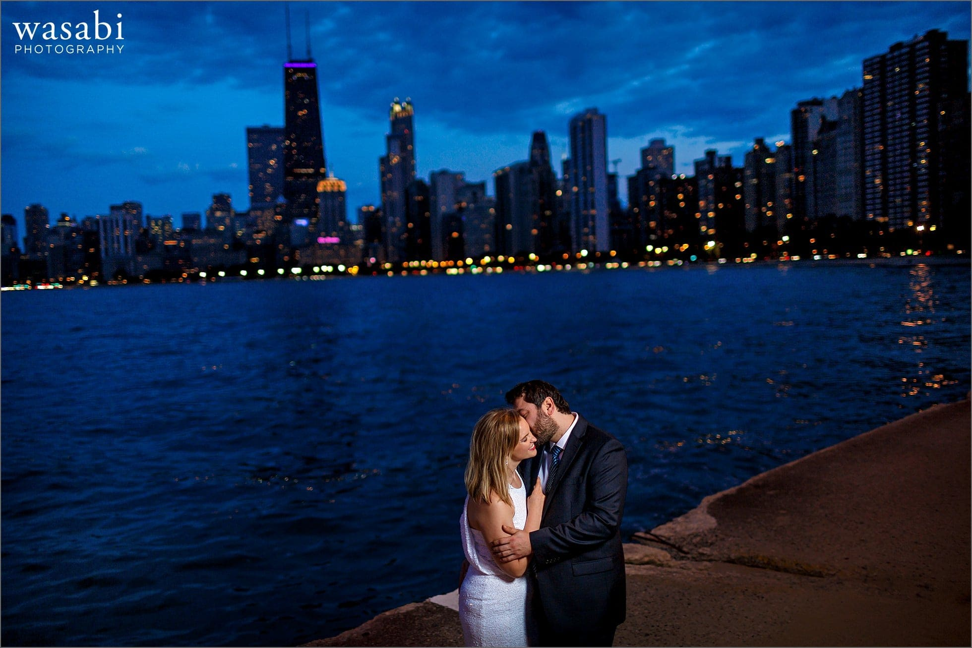 North Avenue beach engagement photos with a couple kissing and the Chicago skyline city lights in the background