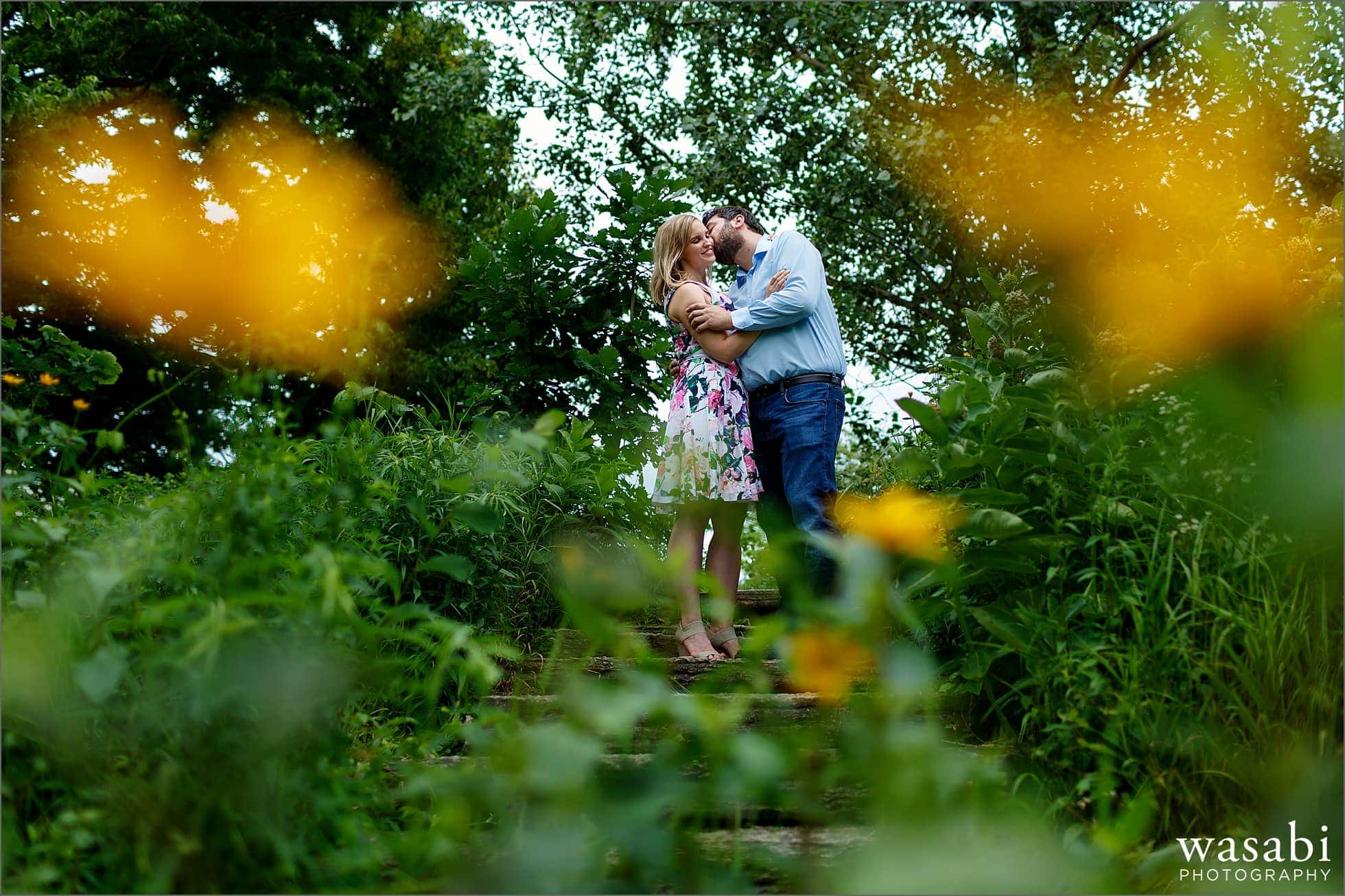 a bride to be gets a kiss on the cheek between a pair of yellow flowers during her engagement session in Alfred Caldwell Lily Pond in Chicagos Lincoln Park