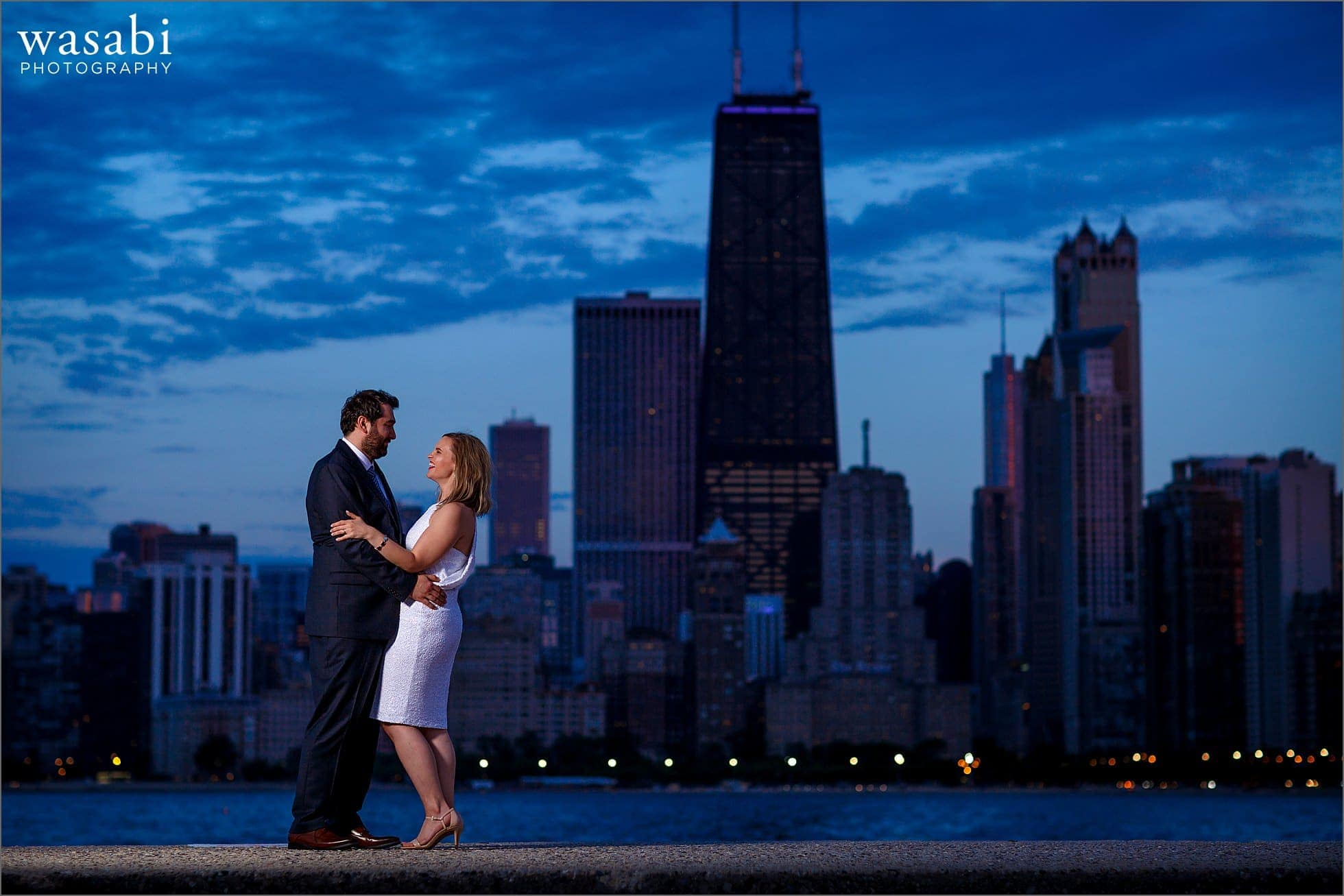 a couple laughs for a North Avenue beach engagement photo with the night time Chicago skyline in the background