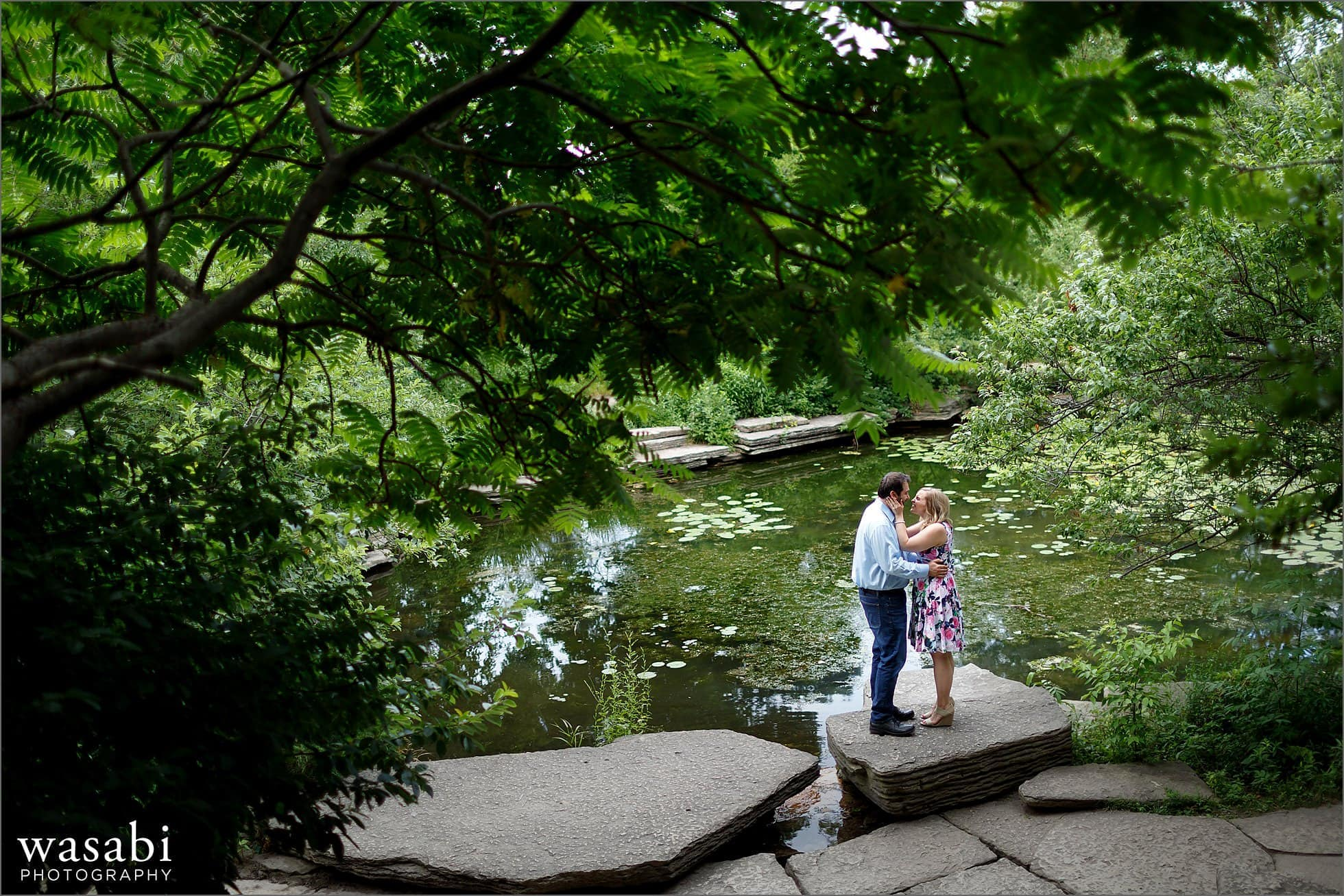 a couple poses for summer engagement photos at Alfred Caldwell Lily Pond in Chicagos Lincoln Park