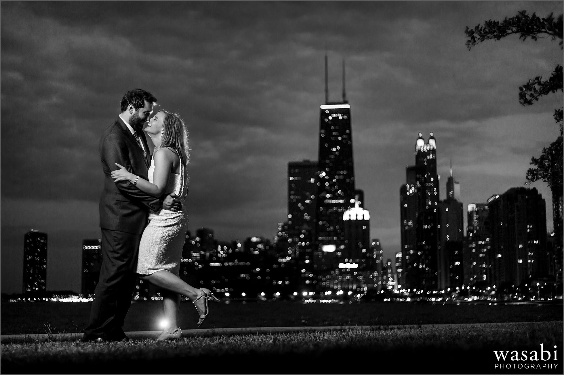backlit, black and white North Avenue Beach engagement photo with a couple laughting during night time Chicago engagement session