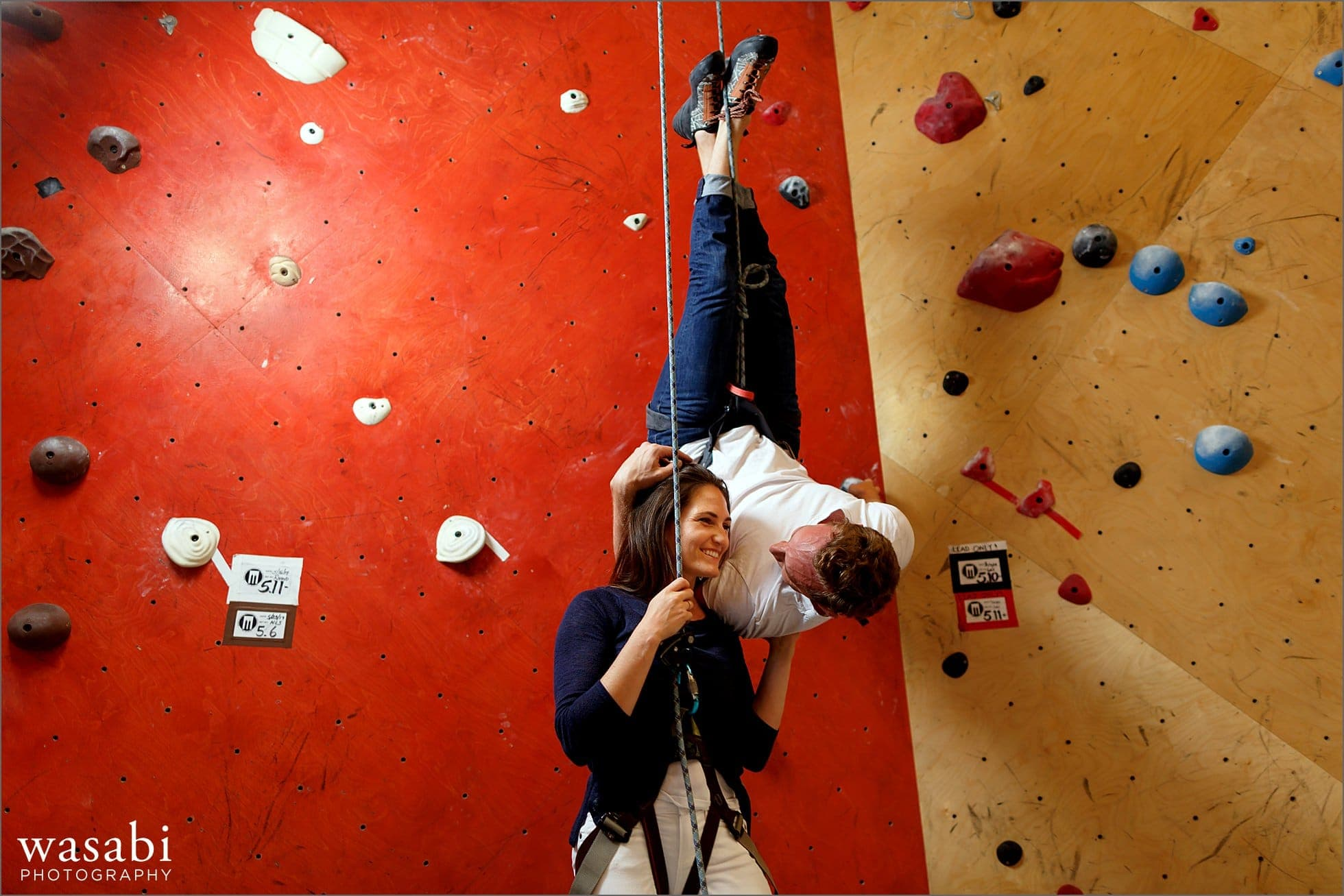 couple laughs poses for Spider Man kiss rock climbing engagement photos at Brooklyn Boulders in Chicagos West Loop neighborhood