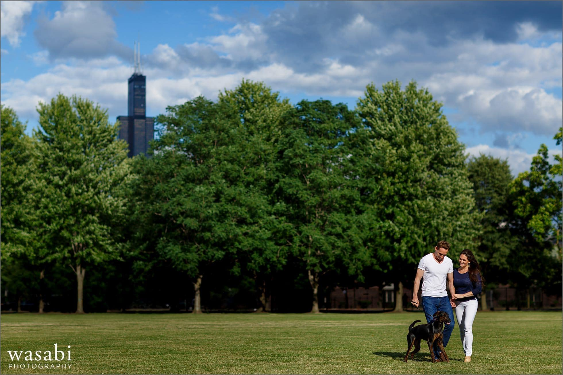 couple walks through Union Park in Chicagos West Loop engagement photos with their dog