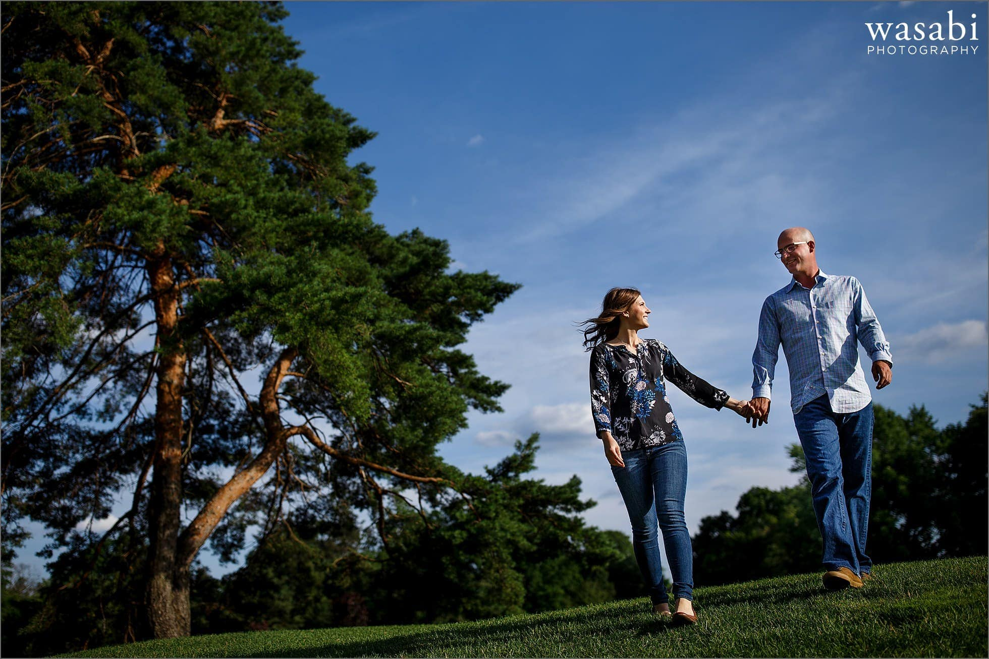 couple holds hands while walking at Red Run Golf Club during their engagement photo session in Royal Oak, Michigan.