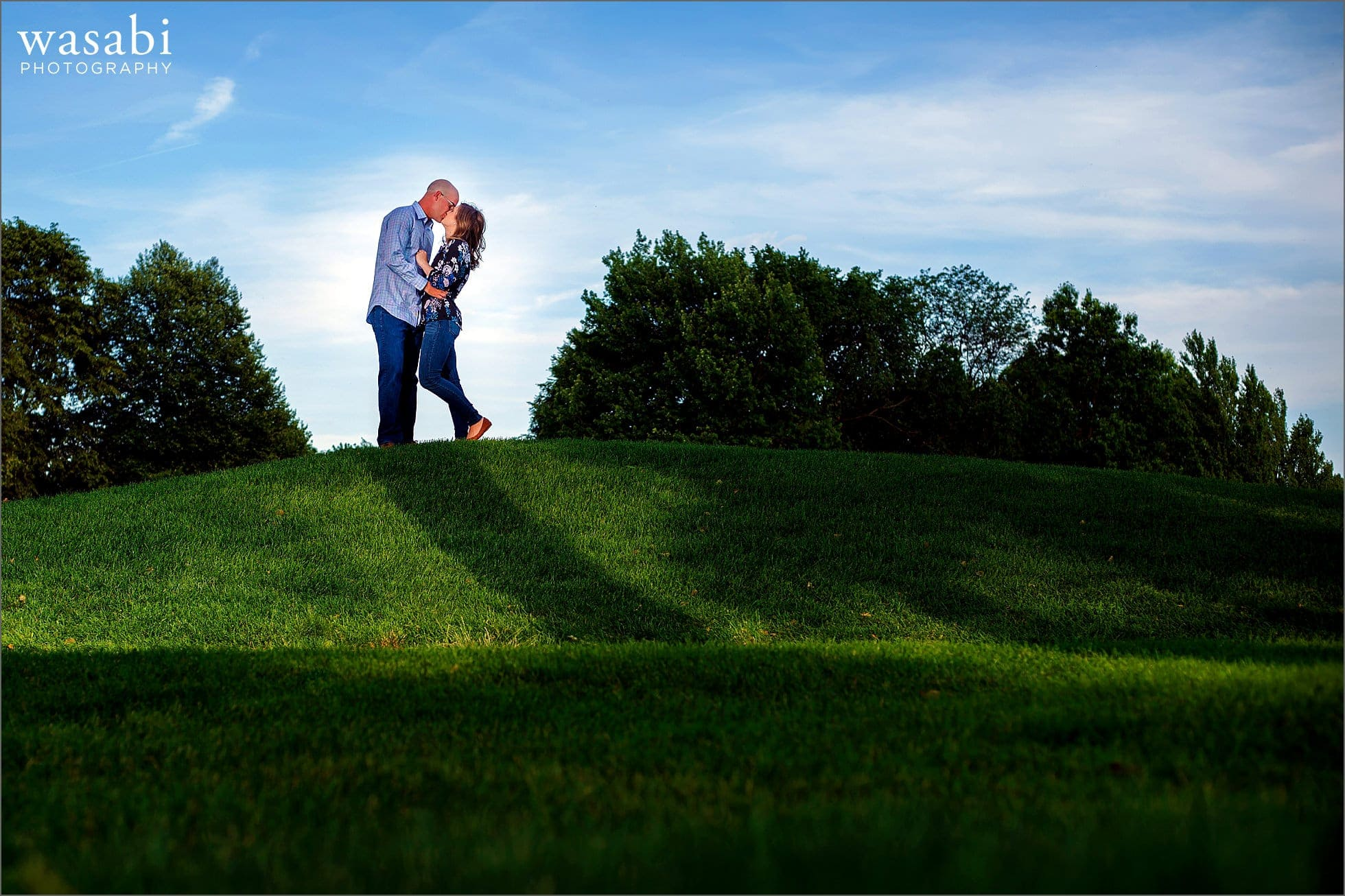 couple kisses on a hill during their engagement photo session at Red Run Golf Club in Royal Oak, Michigan.