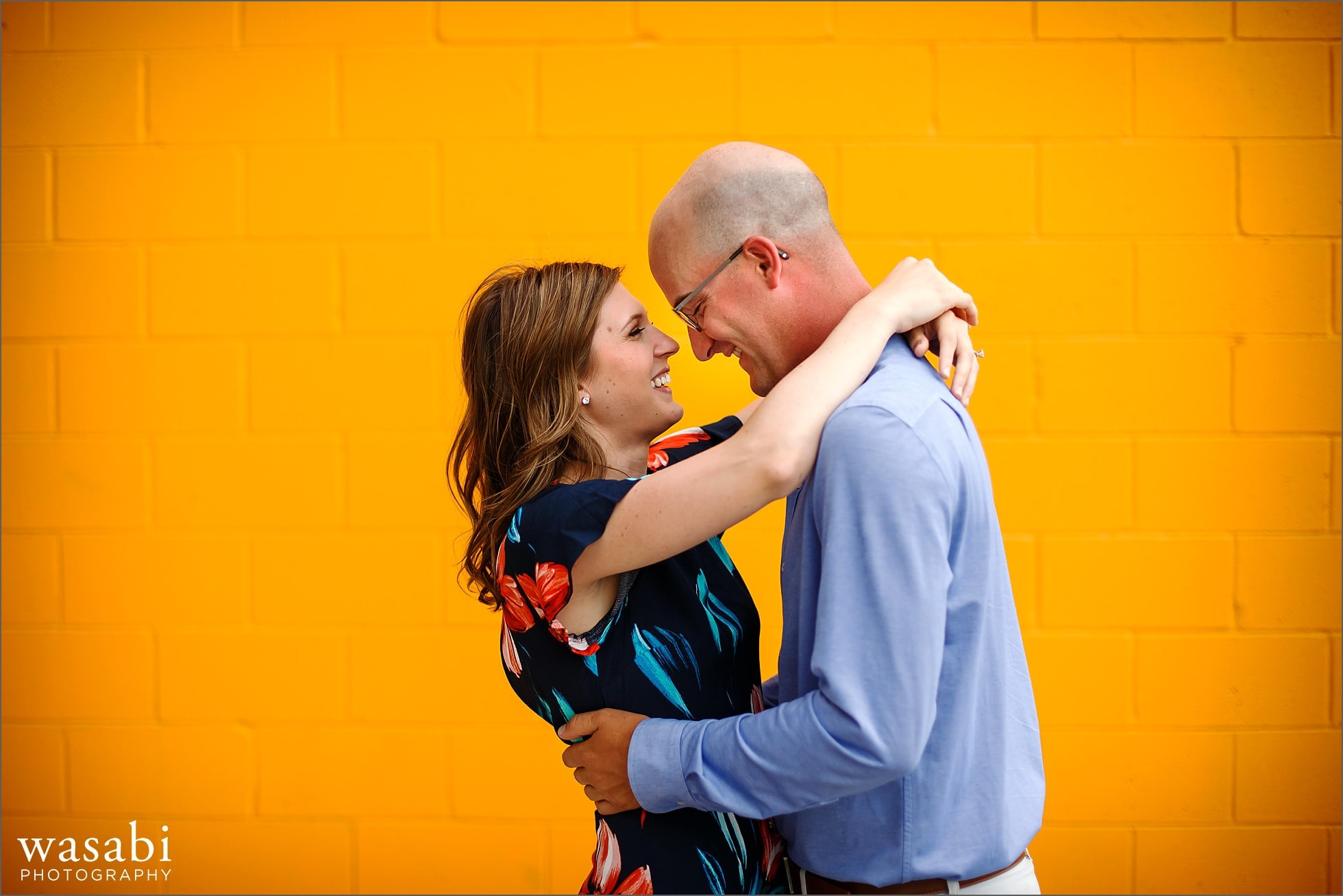 couple poses against a yellow brick wall during their  engagement photos in downtown Royal Oak, Michigan