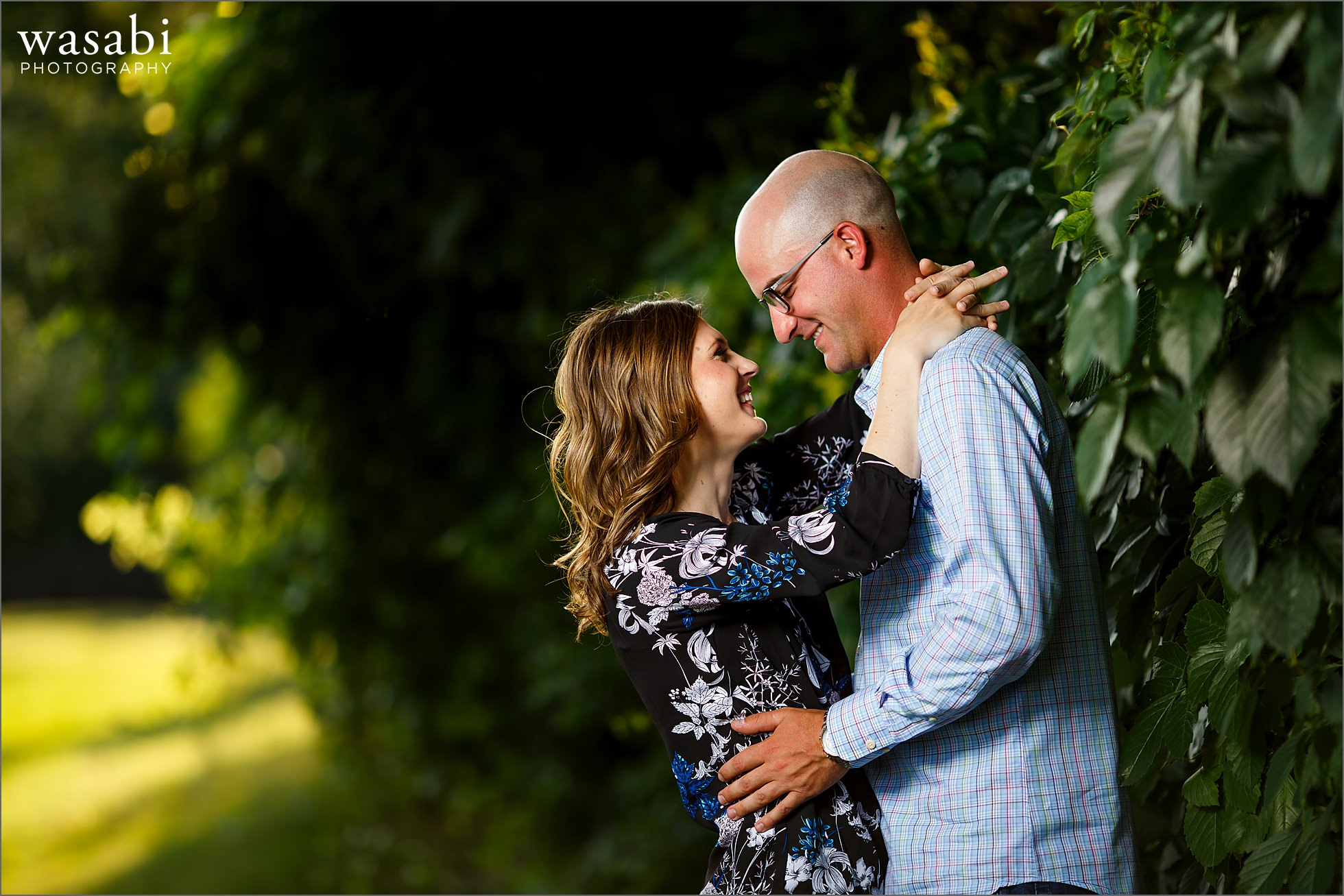 couple poses along a wall of ivy for engagement photos at Red Run Golf Club in Royal Oak, Michigan
