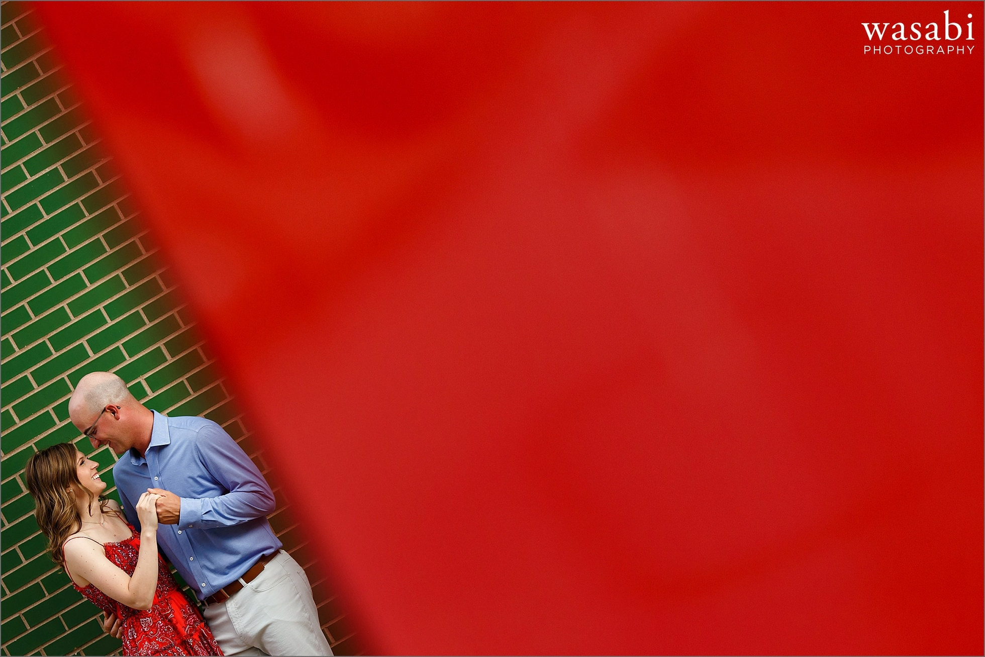 couple poses for colorful engagement photos against green brick wall with red foreground in downtown Royal Oak, Michigan