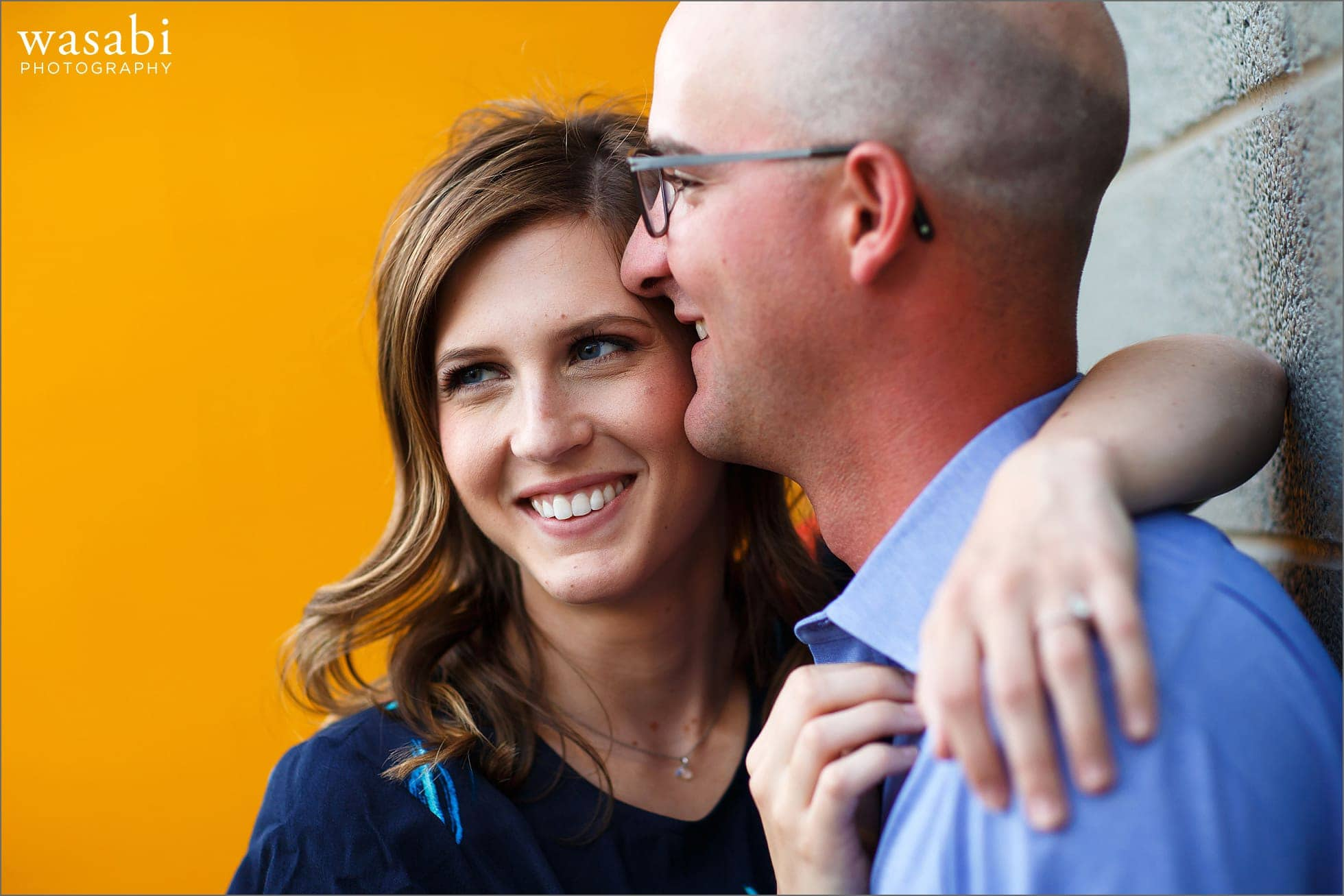 couple poses with a yellow brick wall during their  engagement photos in downtown Royal Oak, Michigan