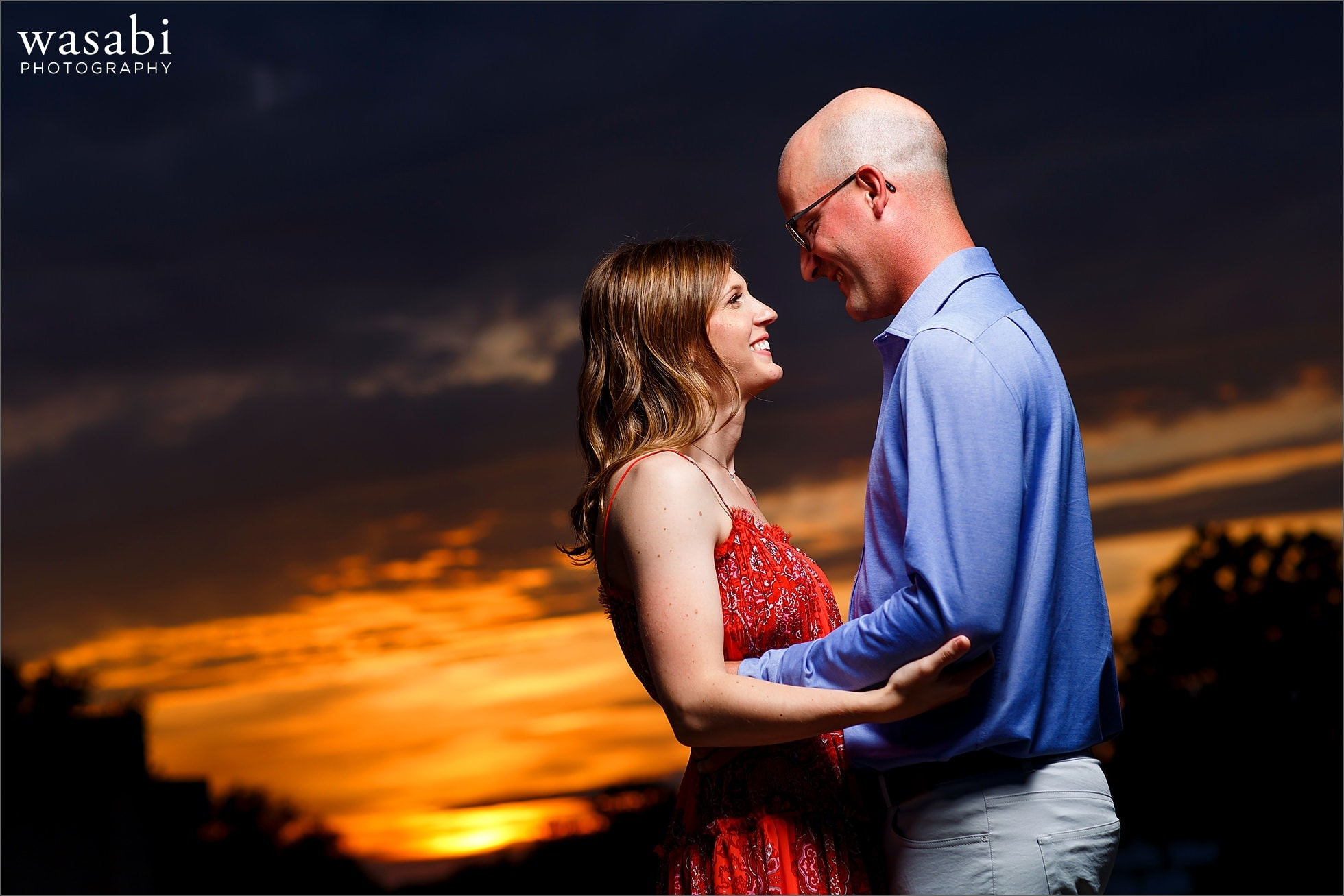 couple poses with sunset in the background during their engagement photo session in downtown Royal Oak, Michigan
