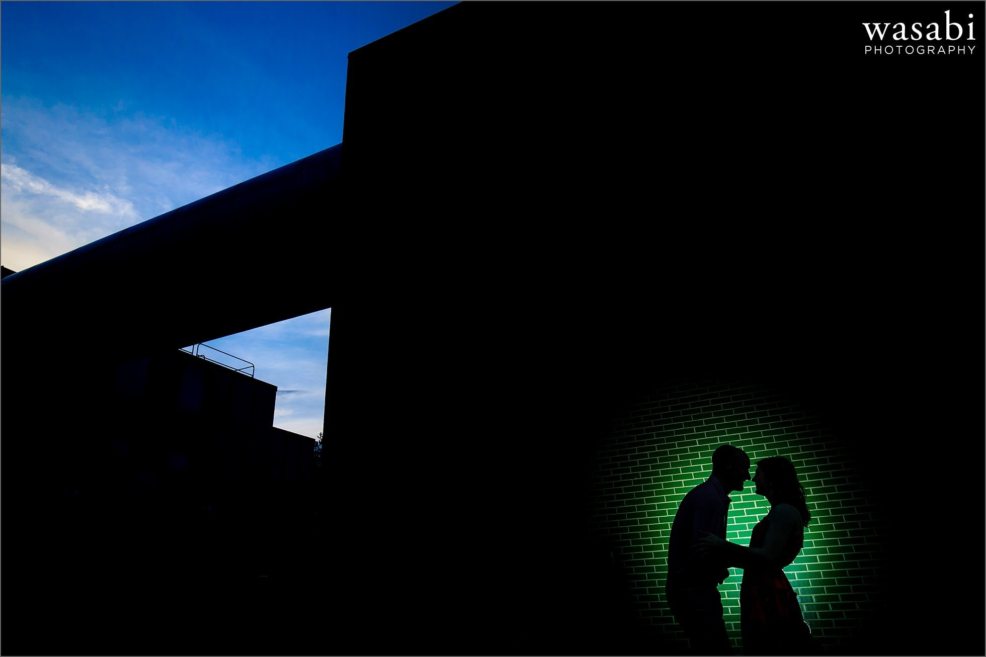 silhouette couple against green brick wall during a colorful engagement photo session in downtown Royal Oak, Michigan