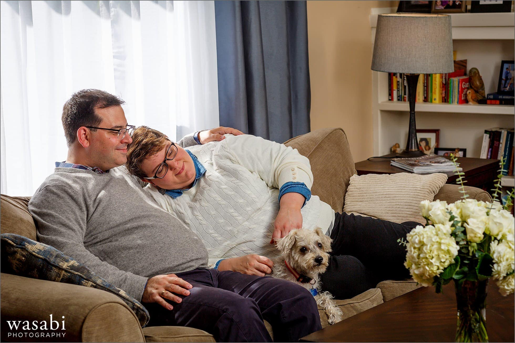 couple lays on the couch with their dog during an in-home engagement session in Boston Lynn Massachusetts
