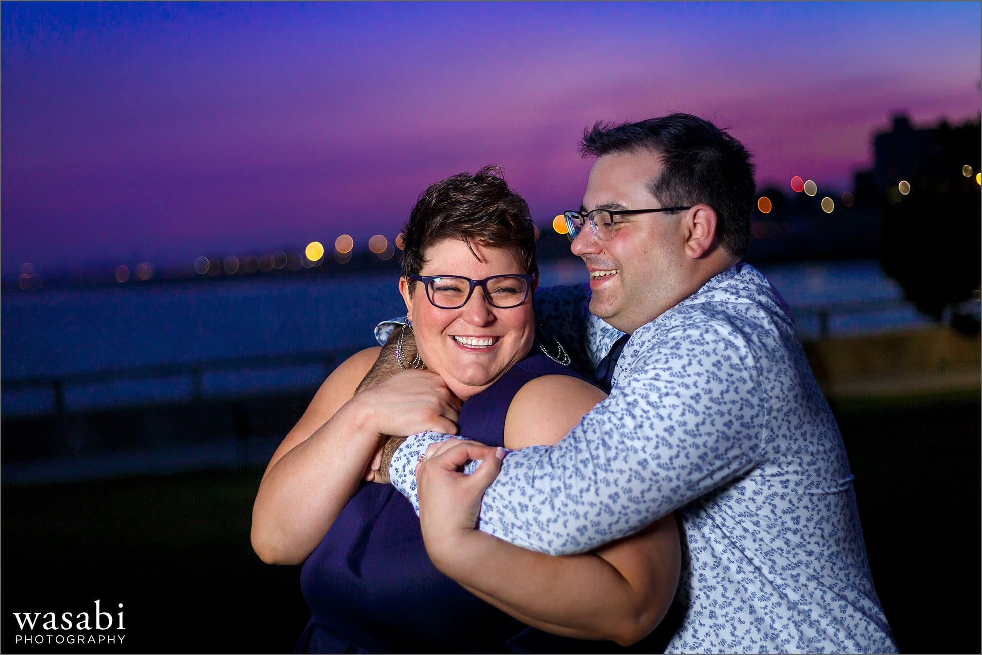 couple poses for Boston skyline engagement photo at Red Rock Park in Lynn Massachusetts