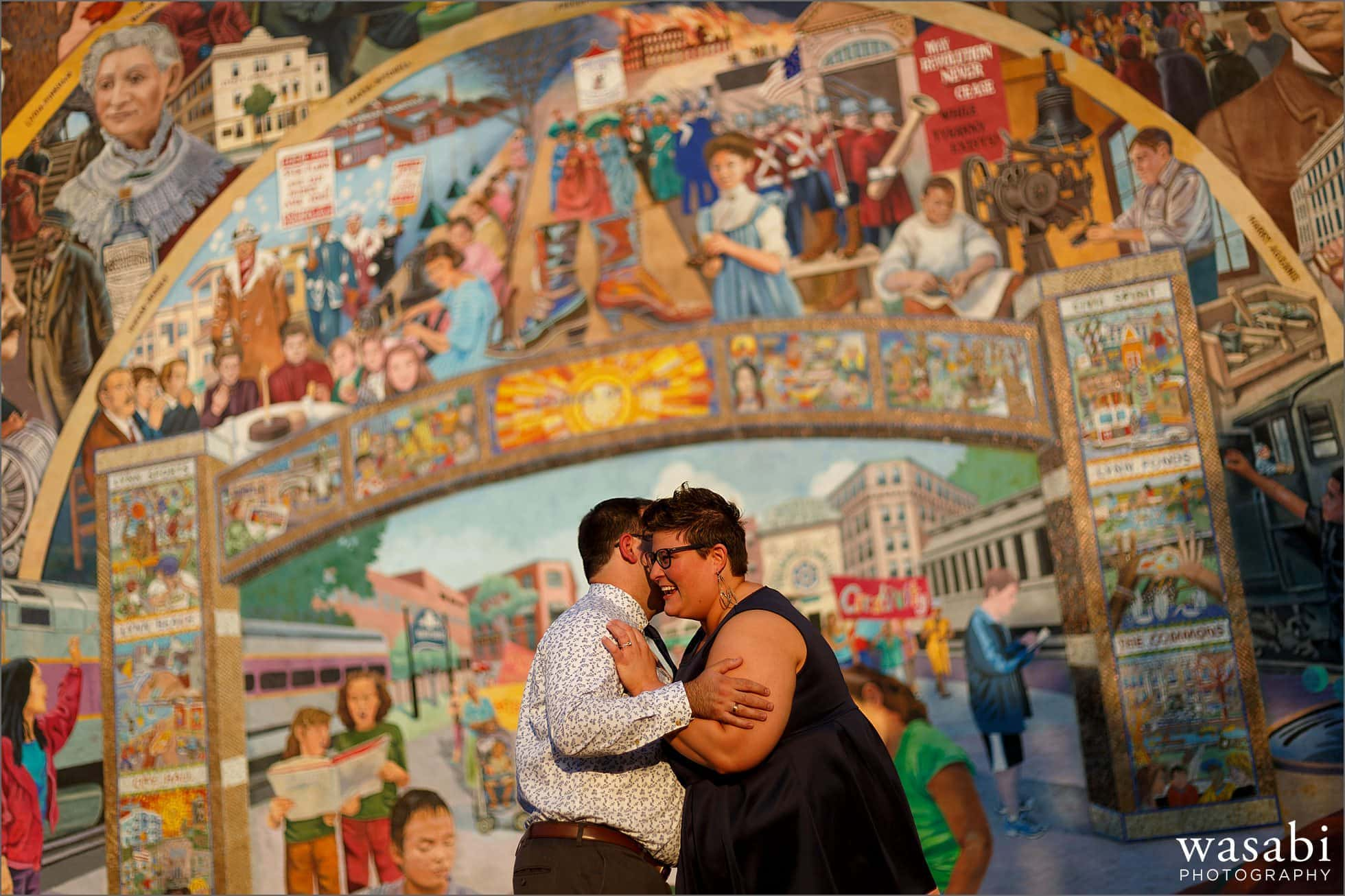 couple poses in front of mural during engagement photos in downtown Lynn Massachusetts
