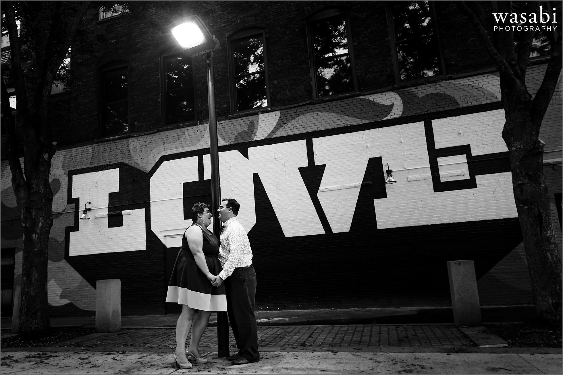 couple poses in front of mural that says LOVE during downtown Lynn Massachusetts engagement session