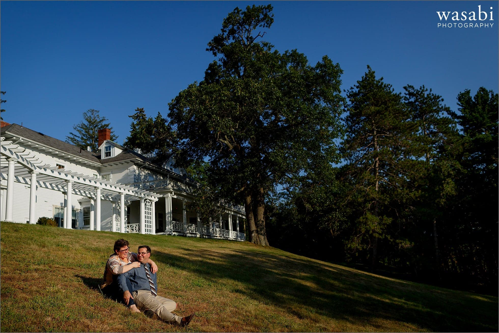 couple sits on the ground during outdoor engagement photos at Spalenza at the Mansion in Peabody Massachusetts while overlooking Suntaug Lake