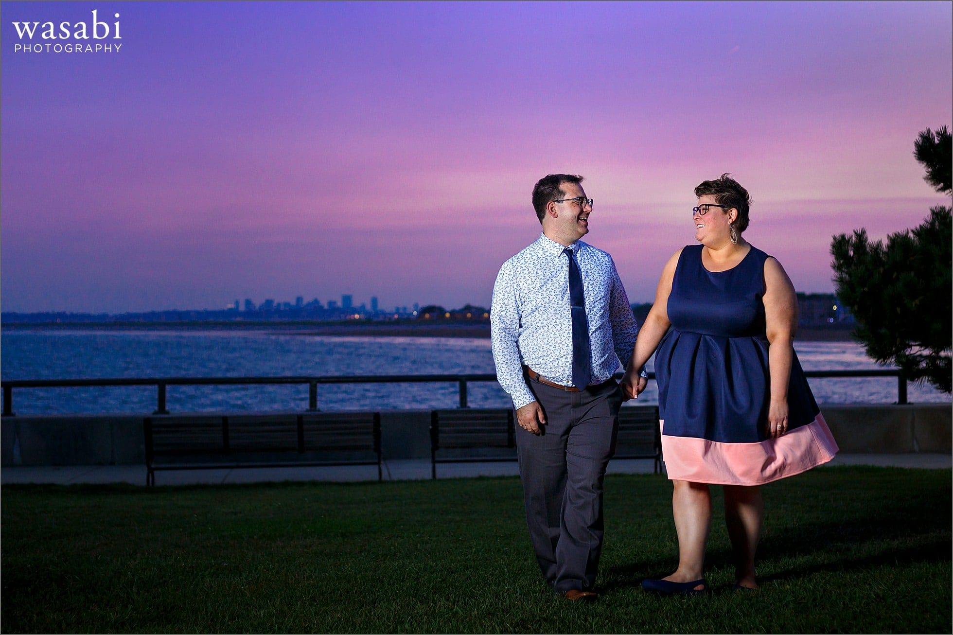 couple walks during Boston skyline engagement photos at Red Rock Park in Lynn Massachusetts