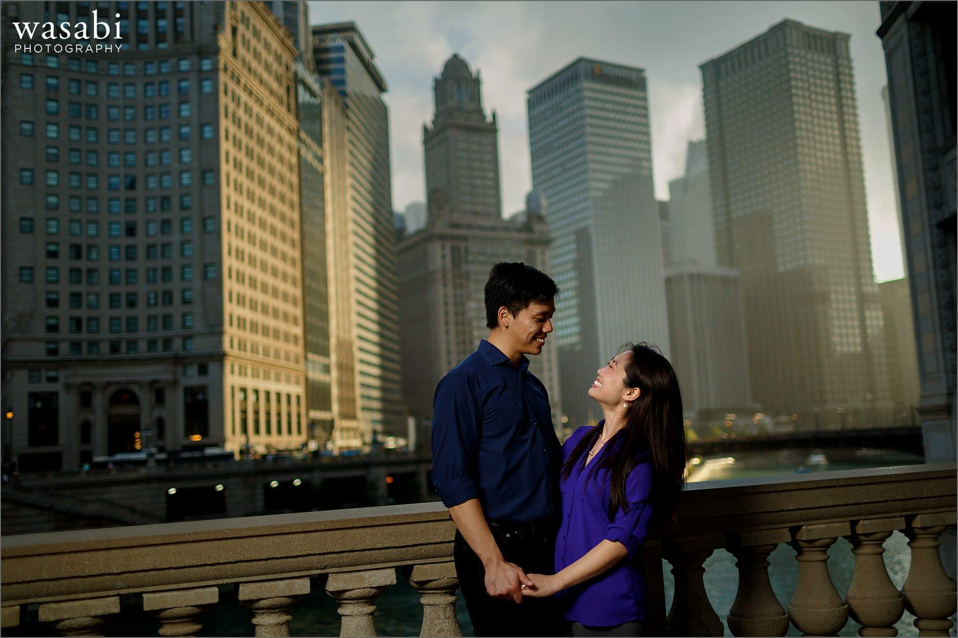 couple kisses during Chicago riverwalk engagement photos in downtown Chicago