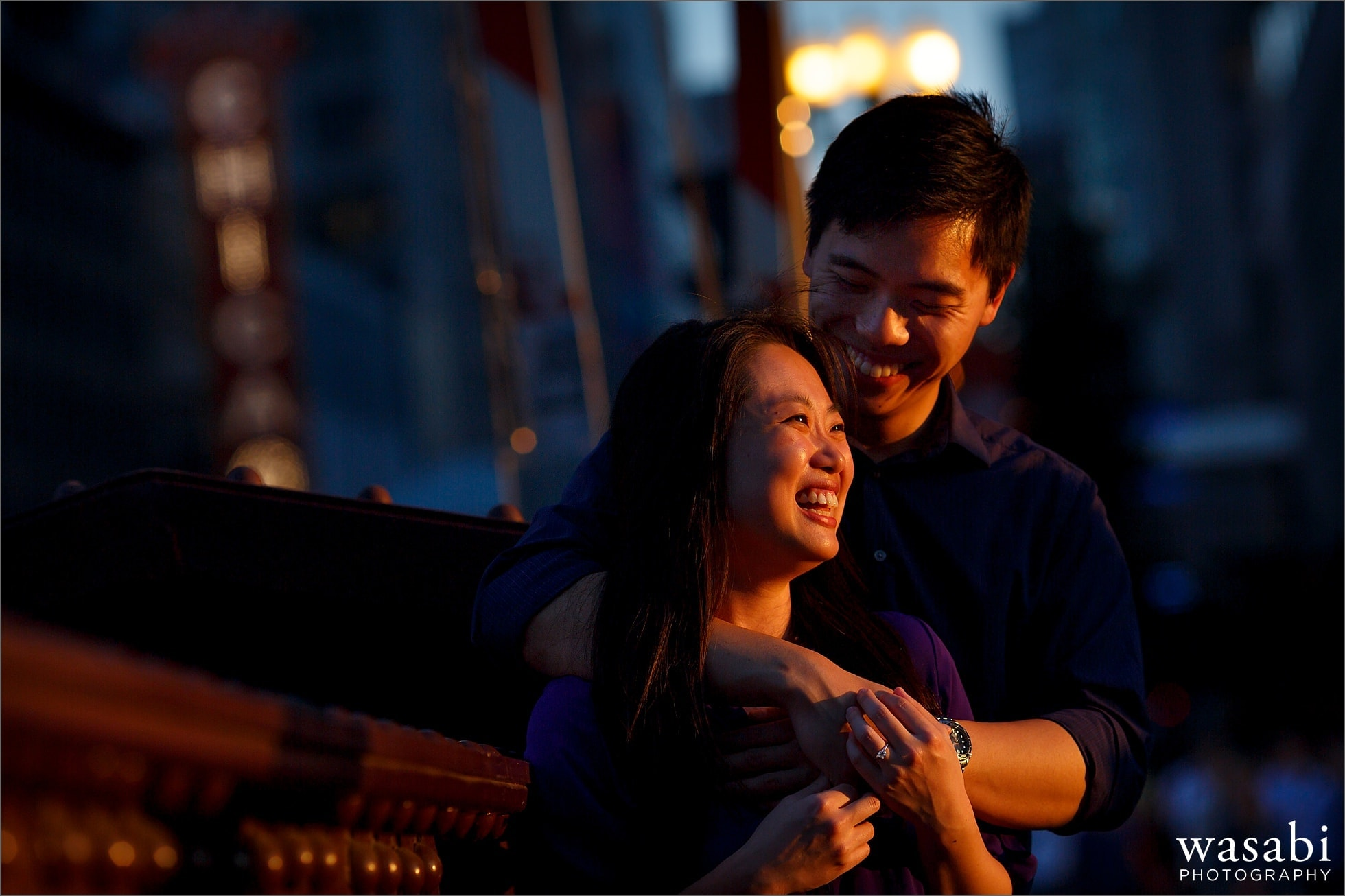 couple laughs during Chicago riverwalk engagement photos on State Street bridge in downtown Chicago