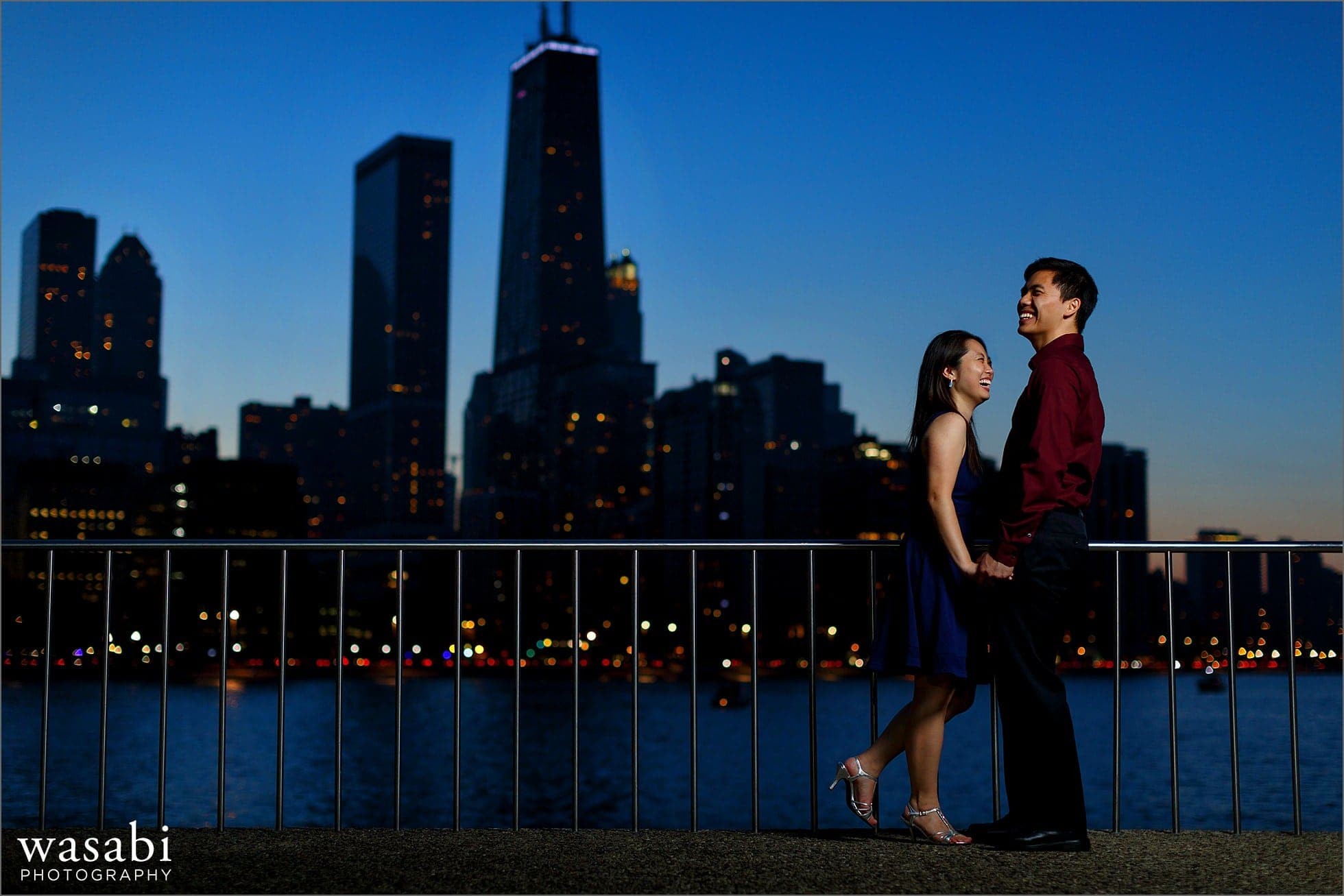 couple laughs during Olive Park engagement photos with Chicago skyline in background