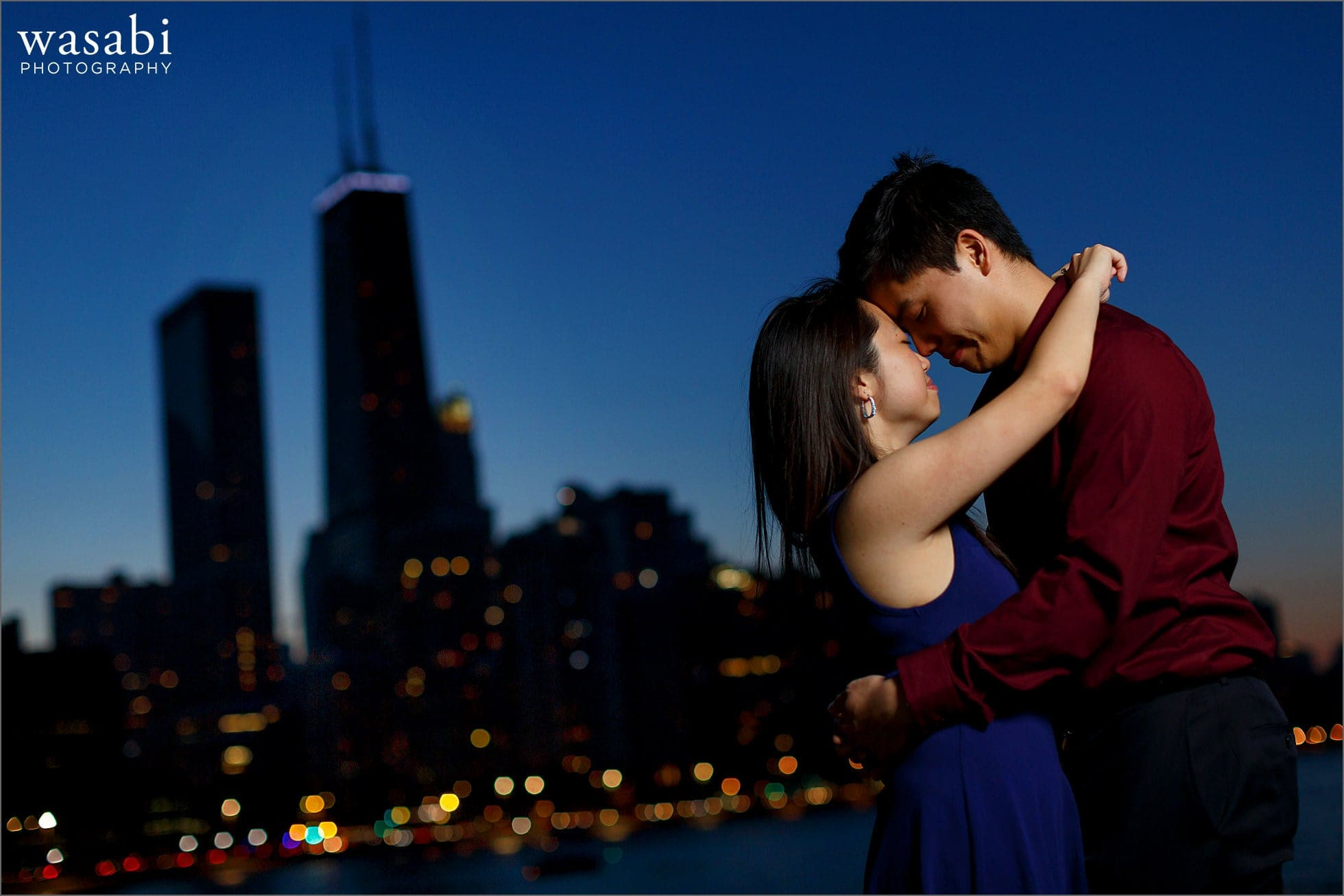 couple poses during Olive Park engagement photos with Chicago skyline in background