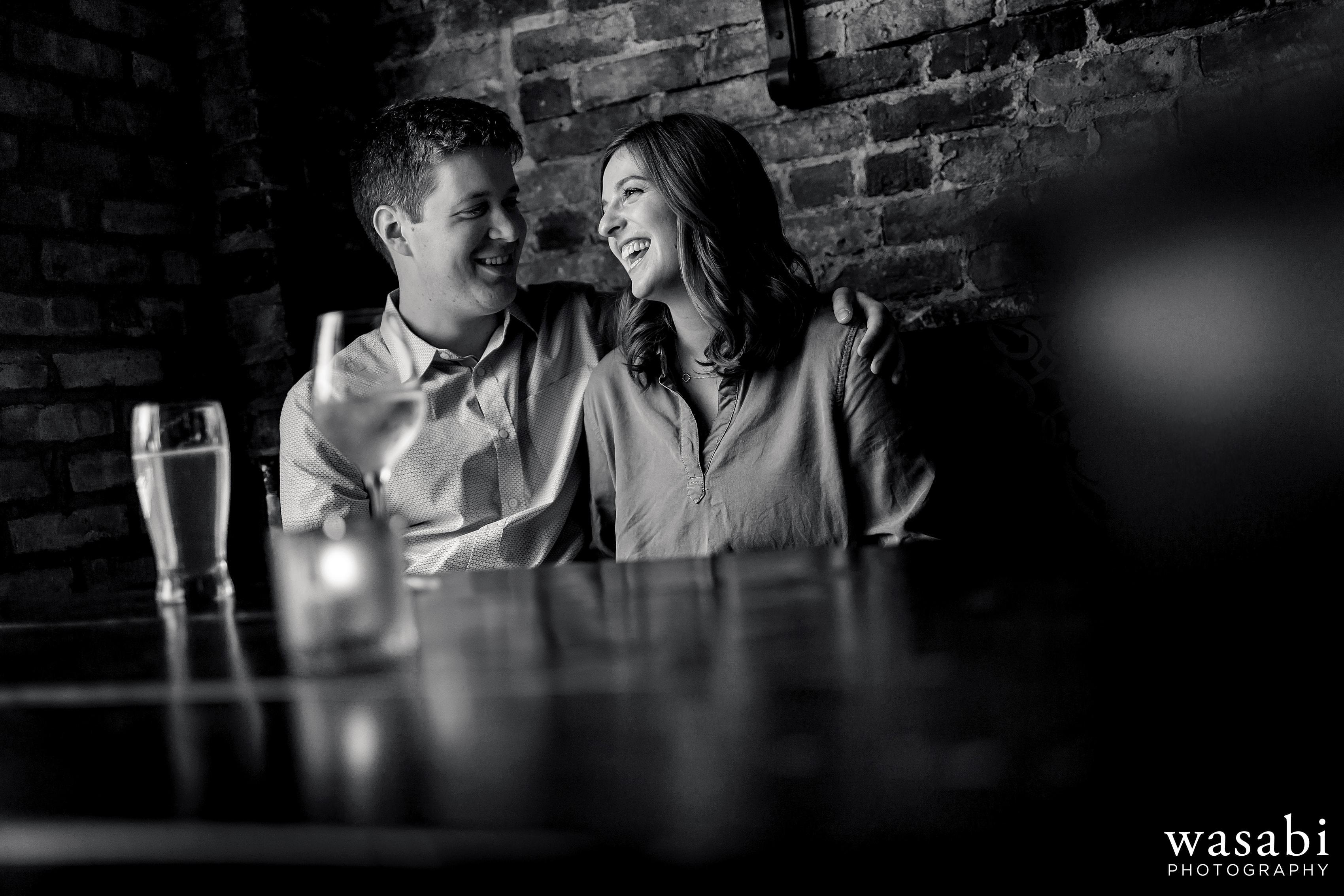 A couple laughs over drinks at Old Town Social during their engagement session in Chicagos Old Town neighborhood