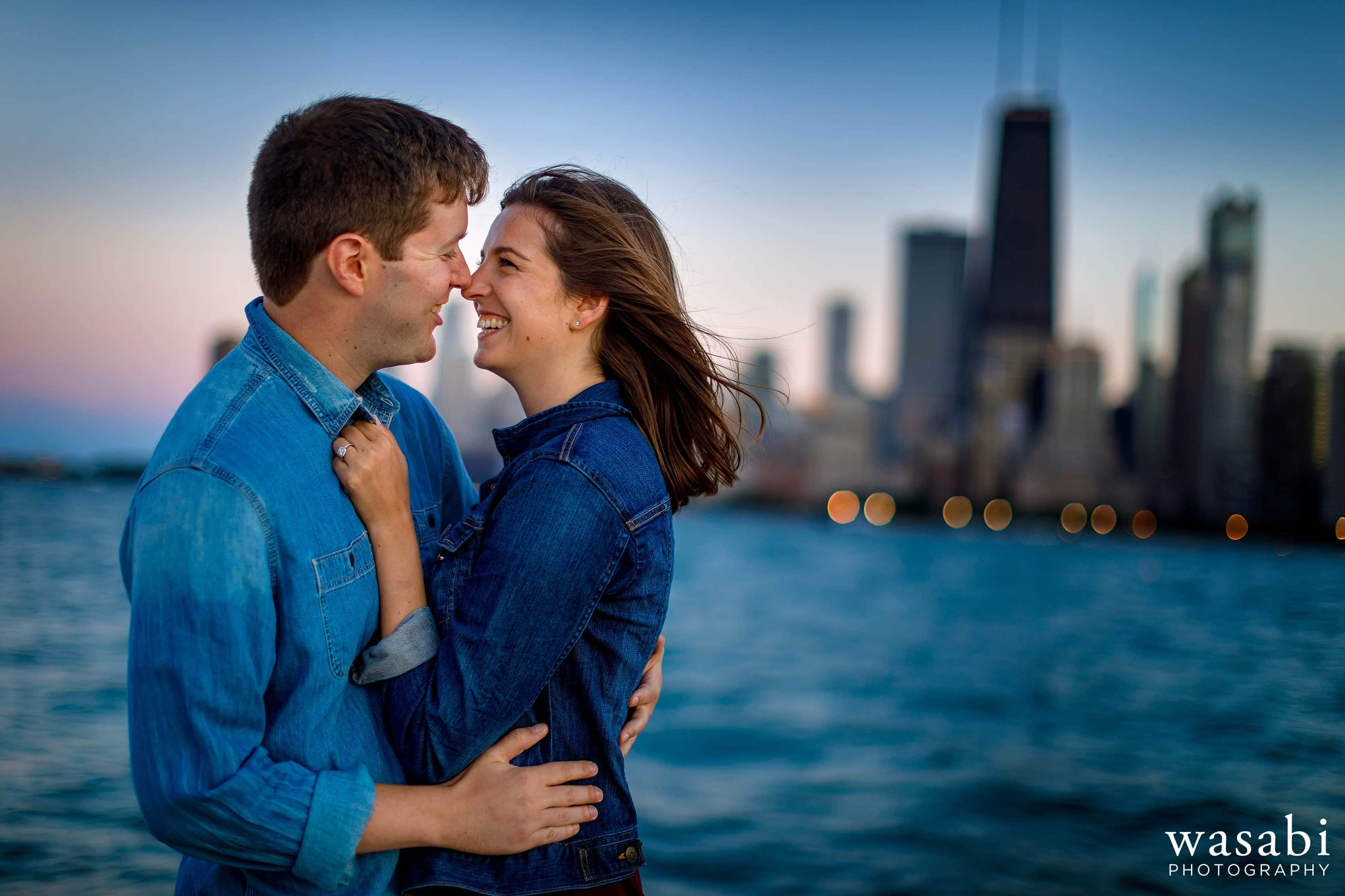 Couple laughs during their North Avenue Engagement Session in Chicago with the skyline in the background
