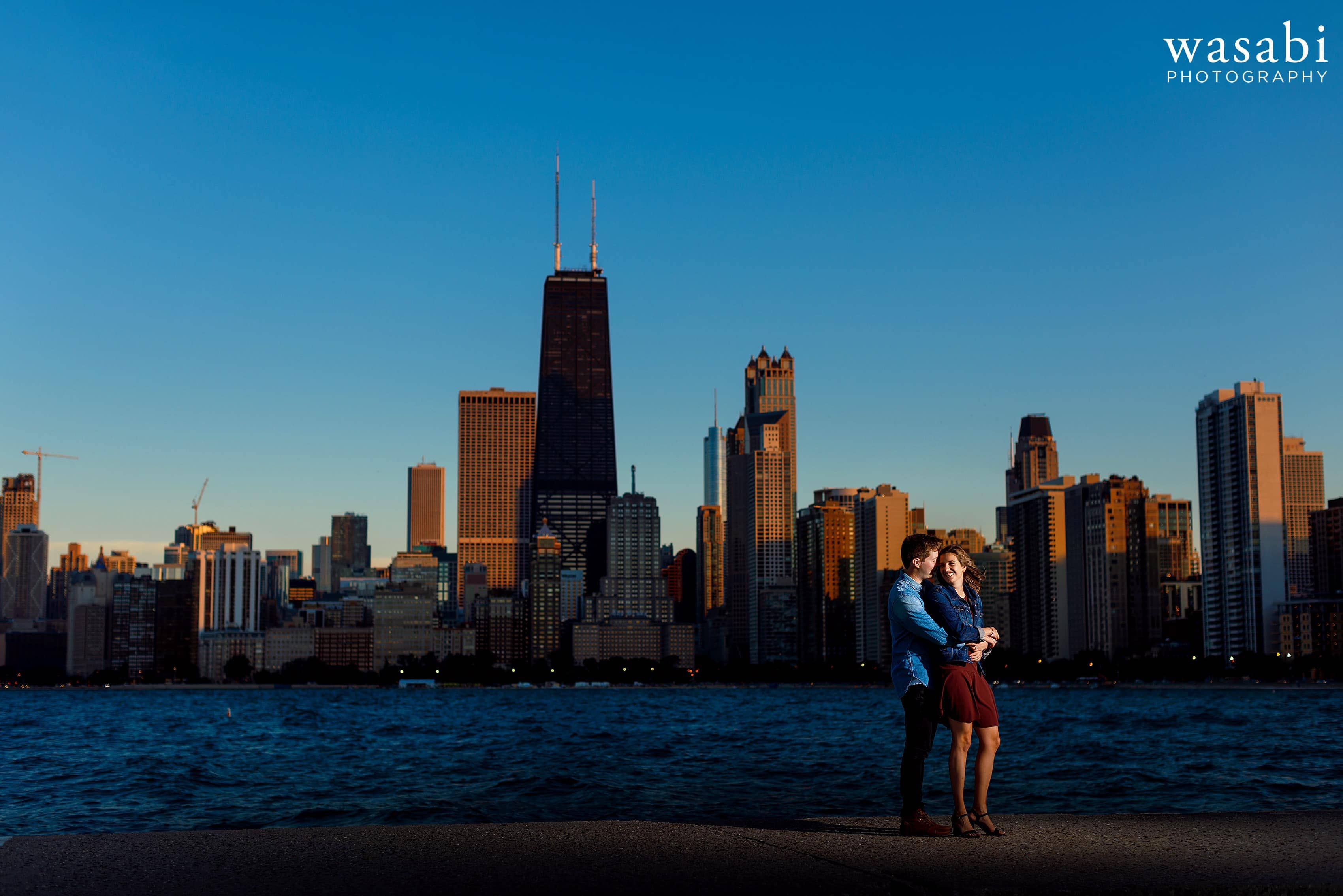 Off camera flash lit photo of a couple posing for engagement photos at North Ave. Beach during their Chicago engagement session with skyline in the background
