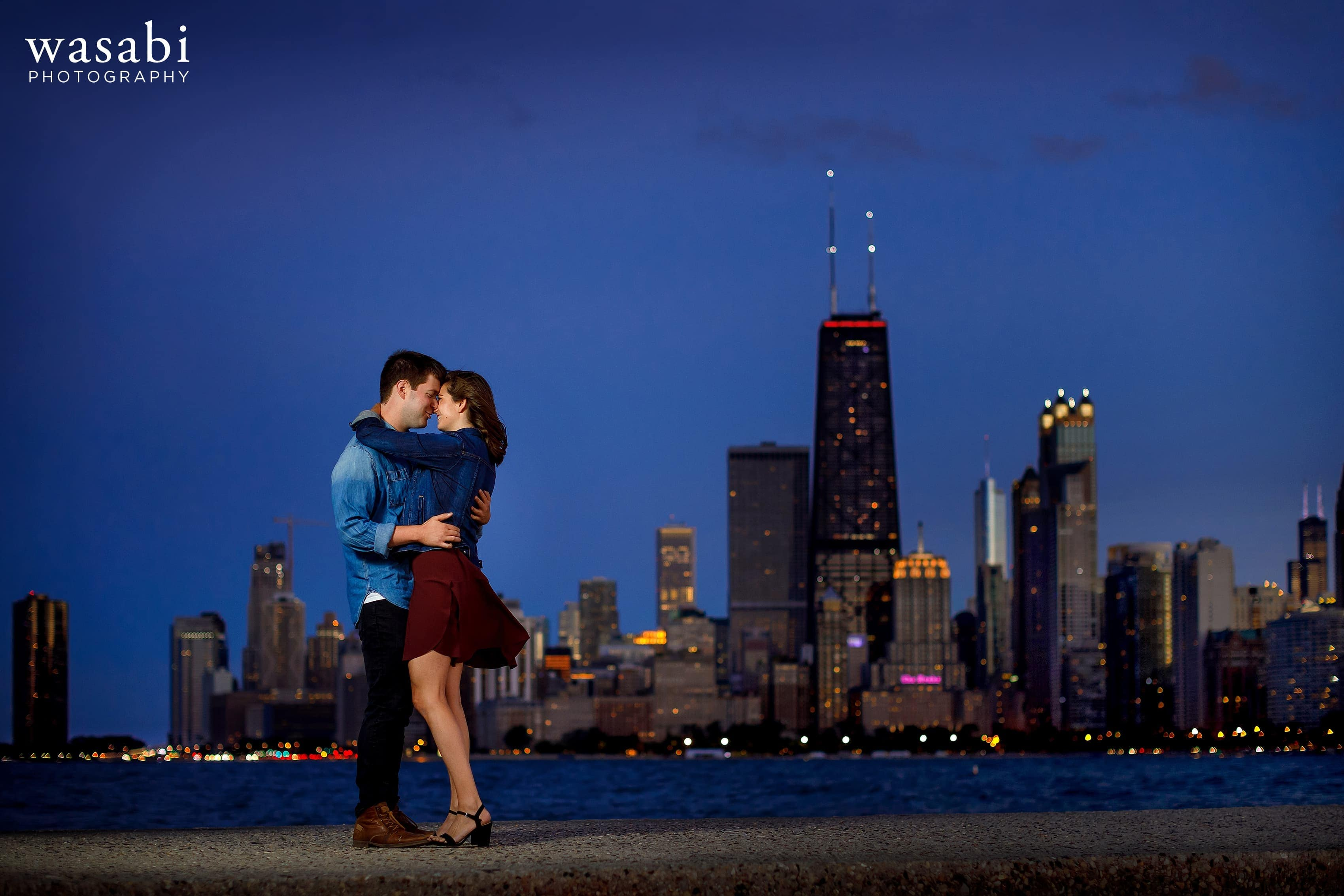 Off camera flash lit photo of a couple posing for engagement photos during their North Avenue Beach engagement session with the Chicago skyline in the background