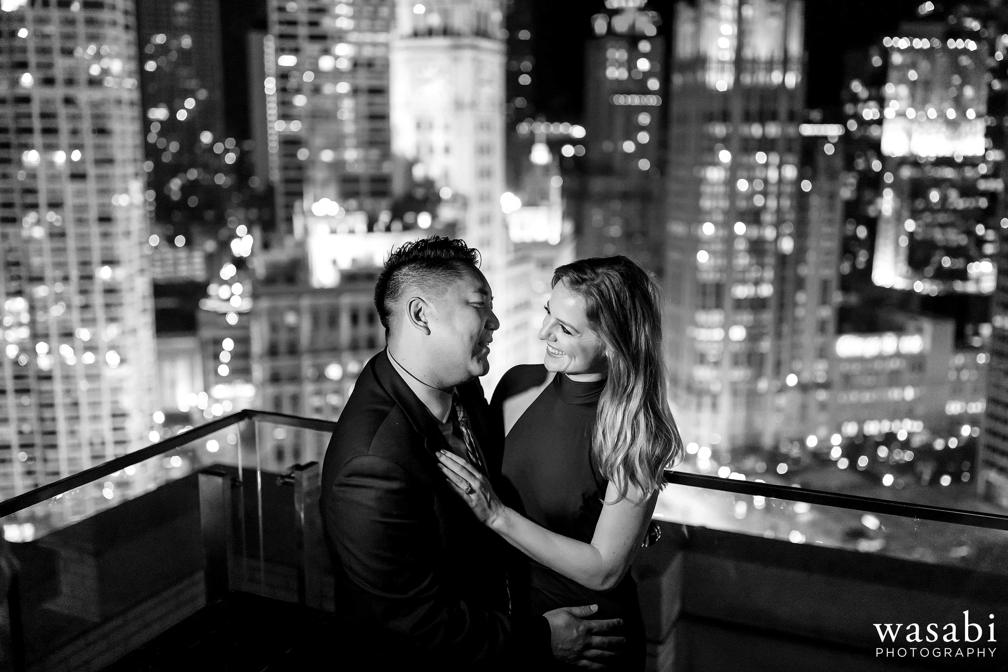 Couple shares drinks during engagement session in downtown Chicago with skyline view from the rooftop bar at London House