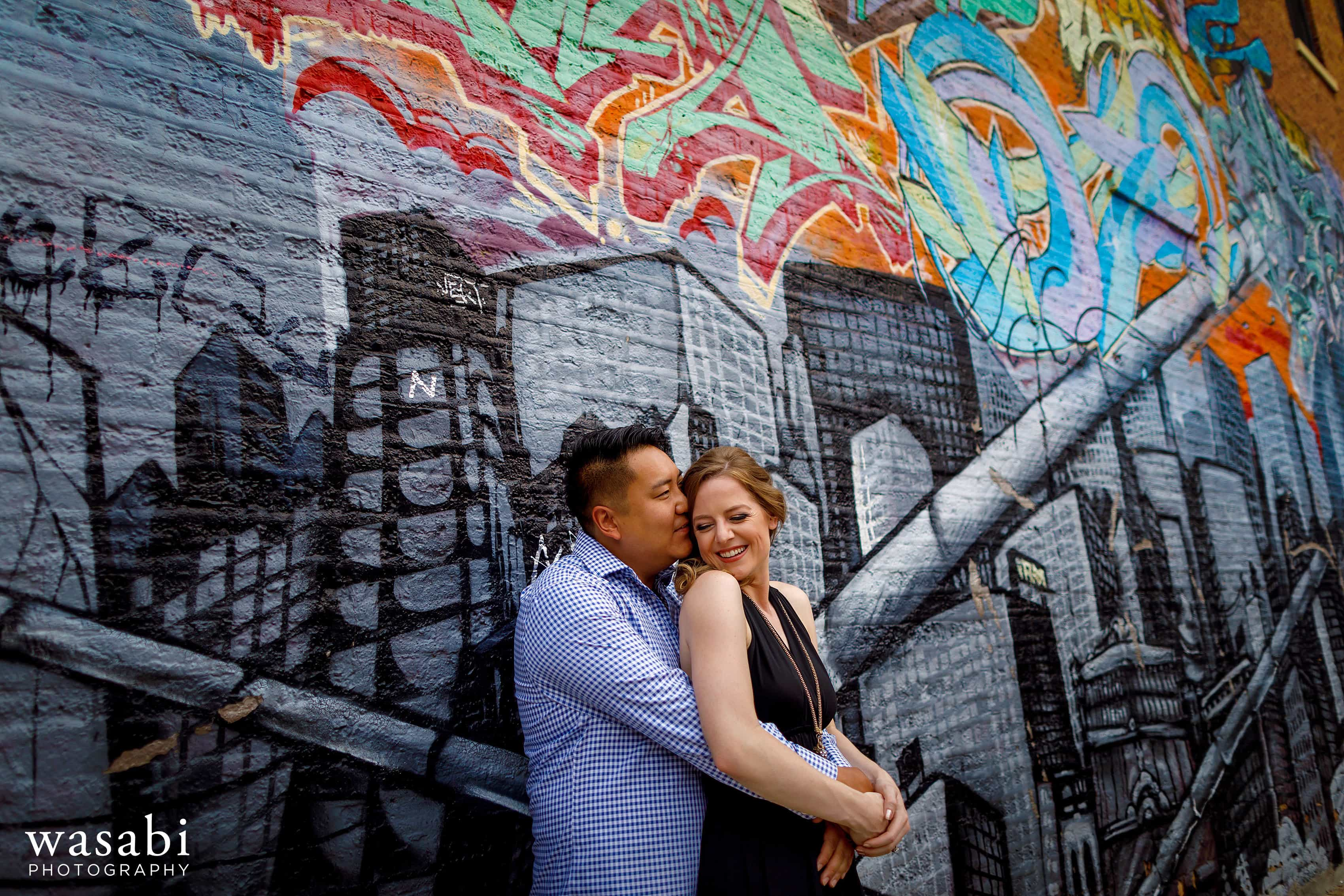 couple in front of mural of chicago skyline buildings in Wicker Park neighborhood during engagement session