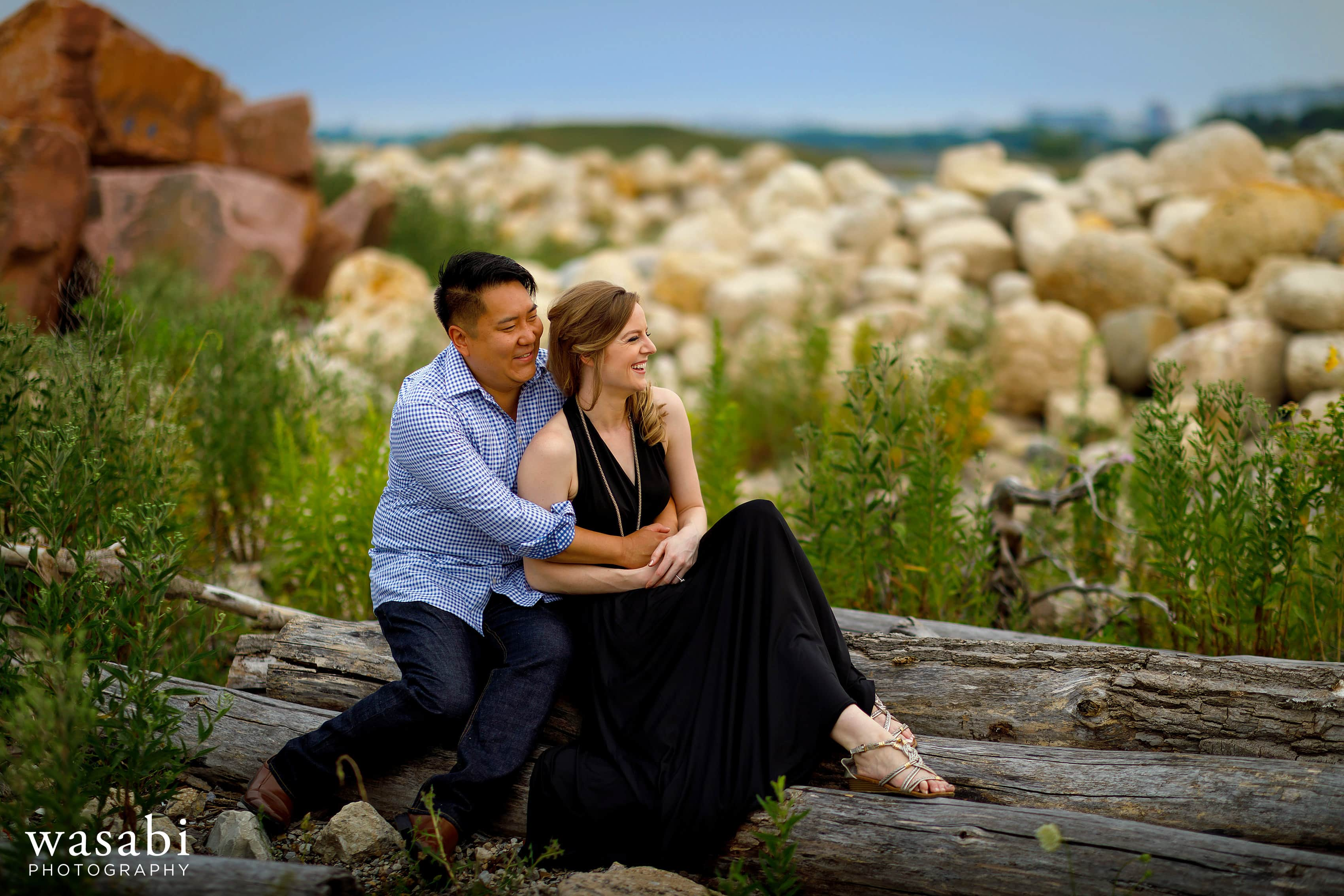 couple sitting on logs with rocks in the background during Northerly Island engagement photos in Chicago
