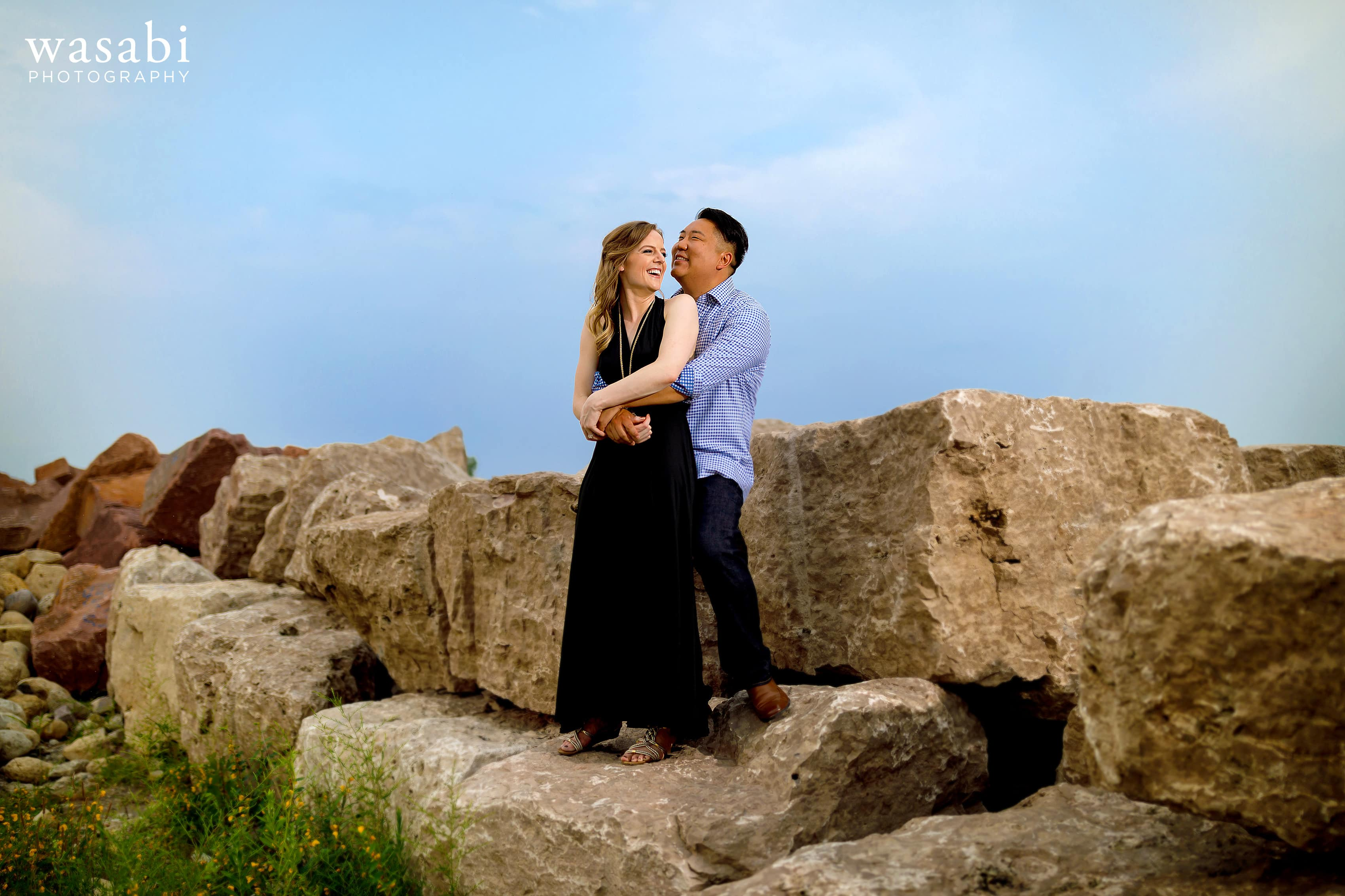 couple standing on huge rocks during Northerly Island engagement photos in Chicago