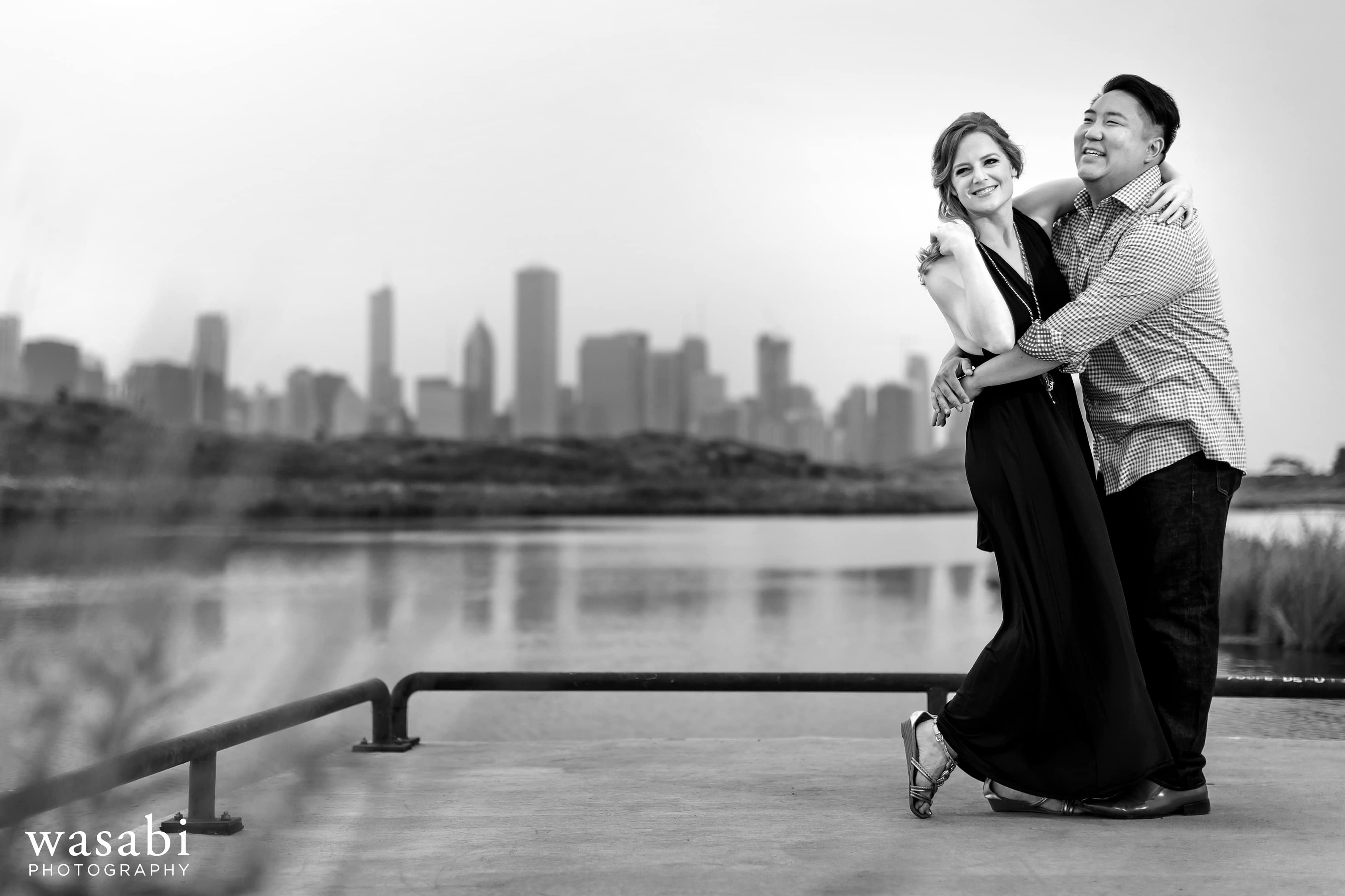 couple standing on pier for Northerly Island engagement photos with Chicago skyline in the background