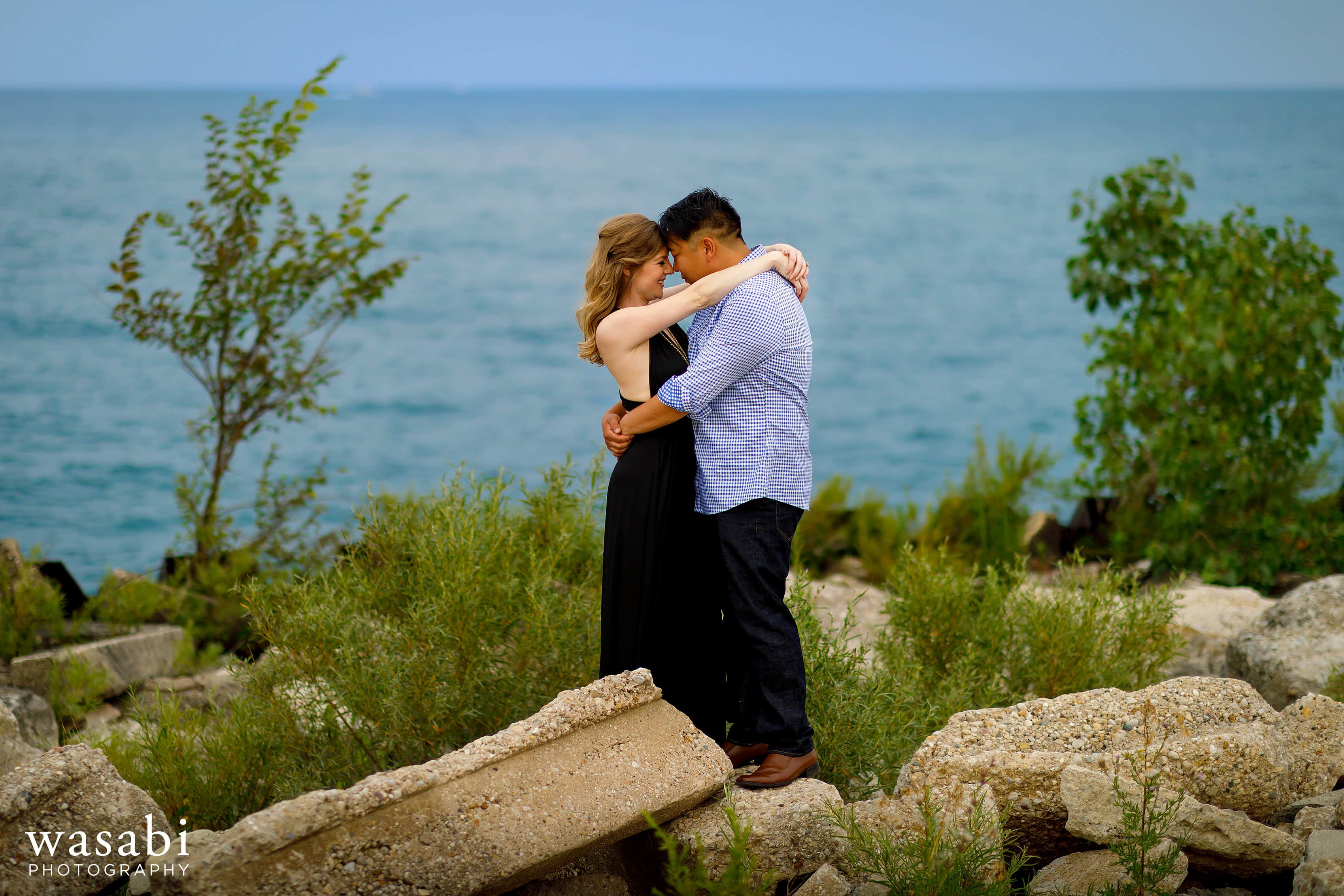 couple standing on rocks at Northerly Island engagement session with Lake Michigan in the background in Chicago