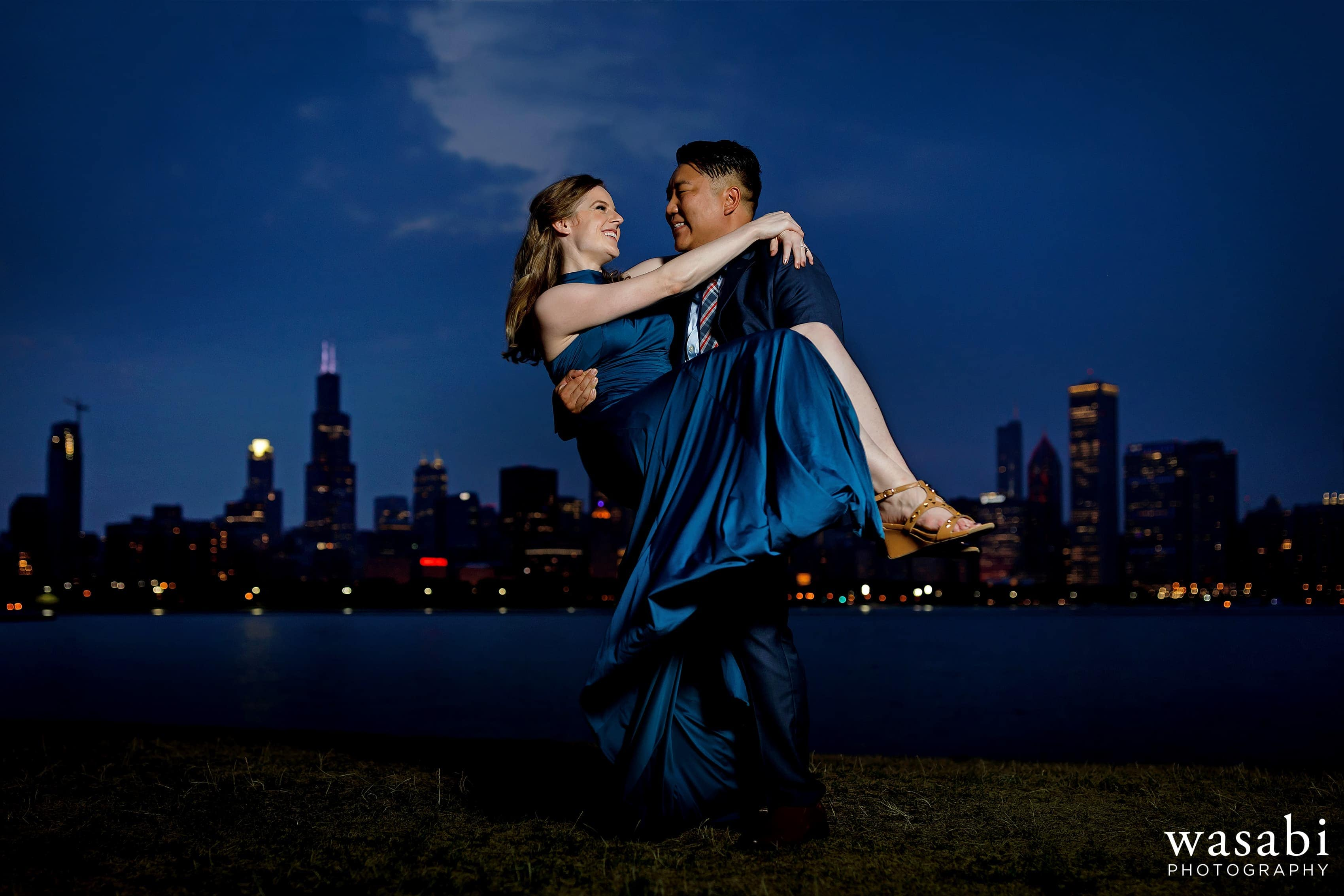 groom picks up bride at Adler Planetarium with Chicago skyline in the background during Museum Campus engagement session
