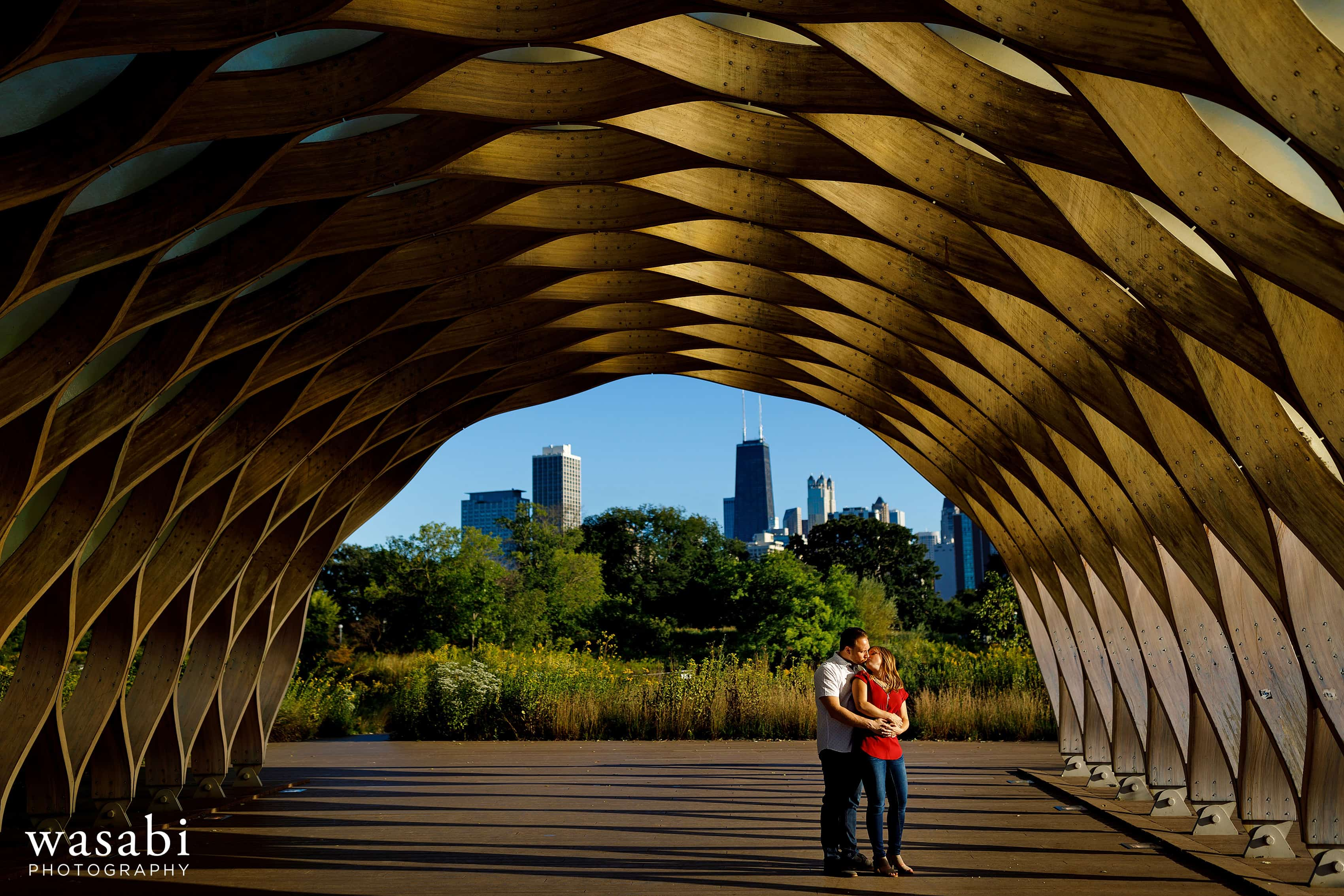 Couple kisses under Lincoln Park honeycomb wood arch Peoples Gas Education Pavilion during their engagement session in Chicago