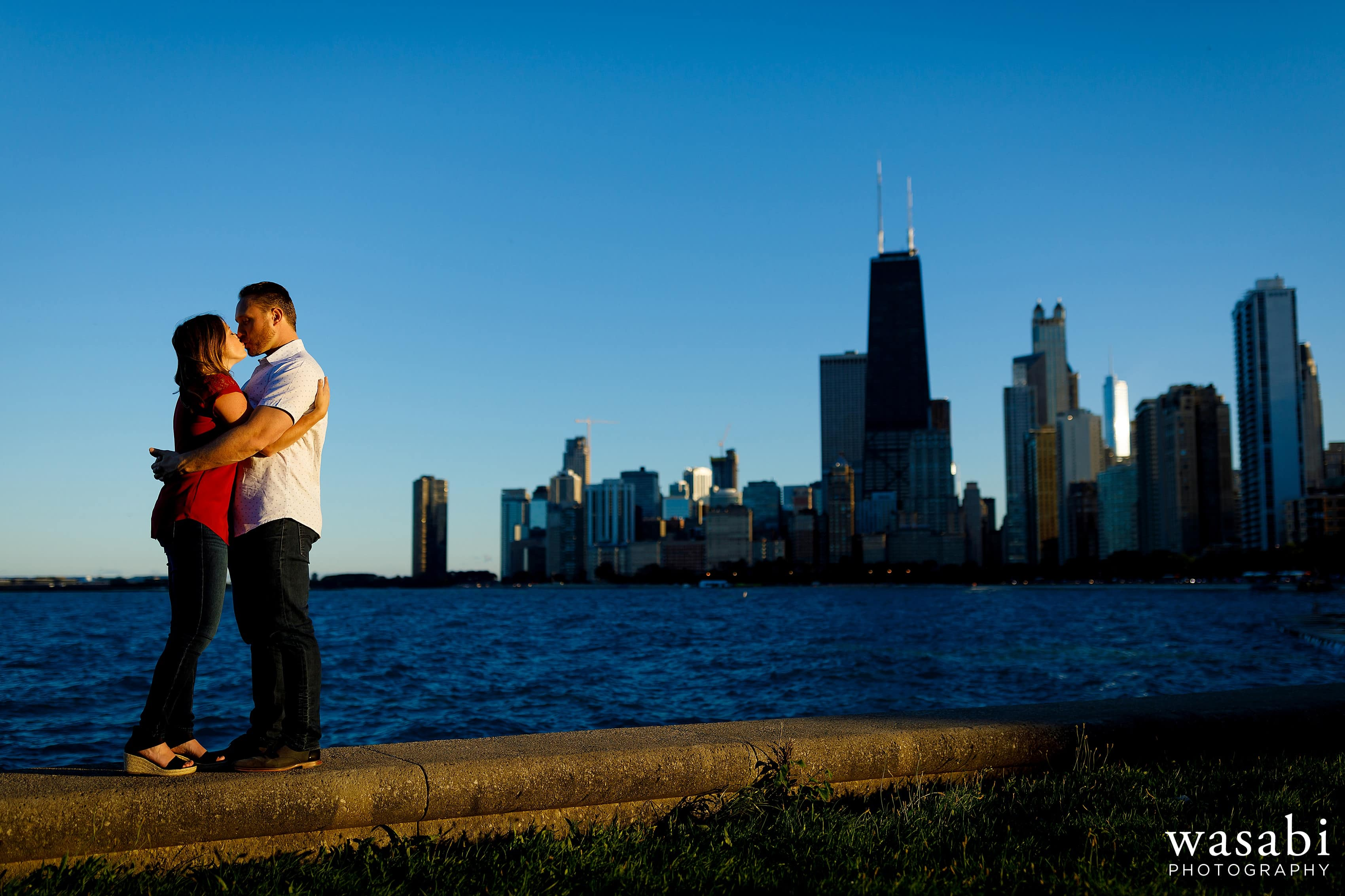 Couple poses along Lake Michigan during engagement photos at North Ave. Beach with Chicago skyline in the background