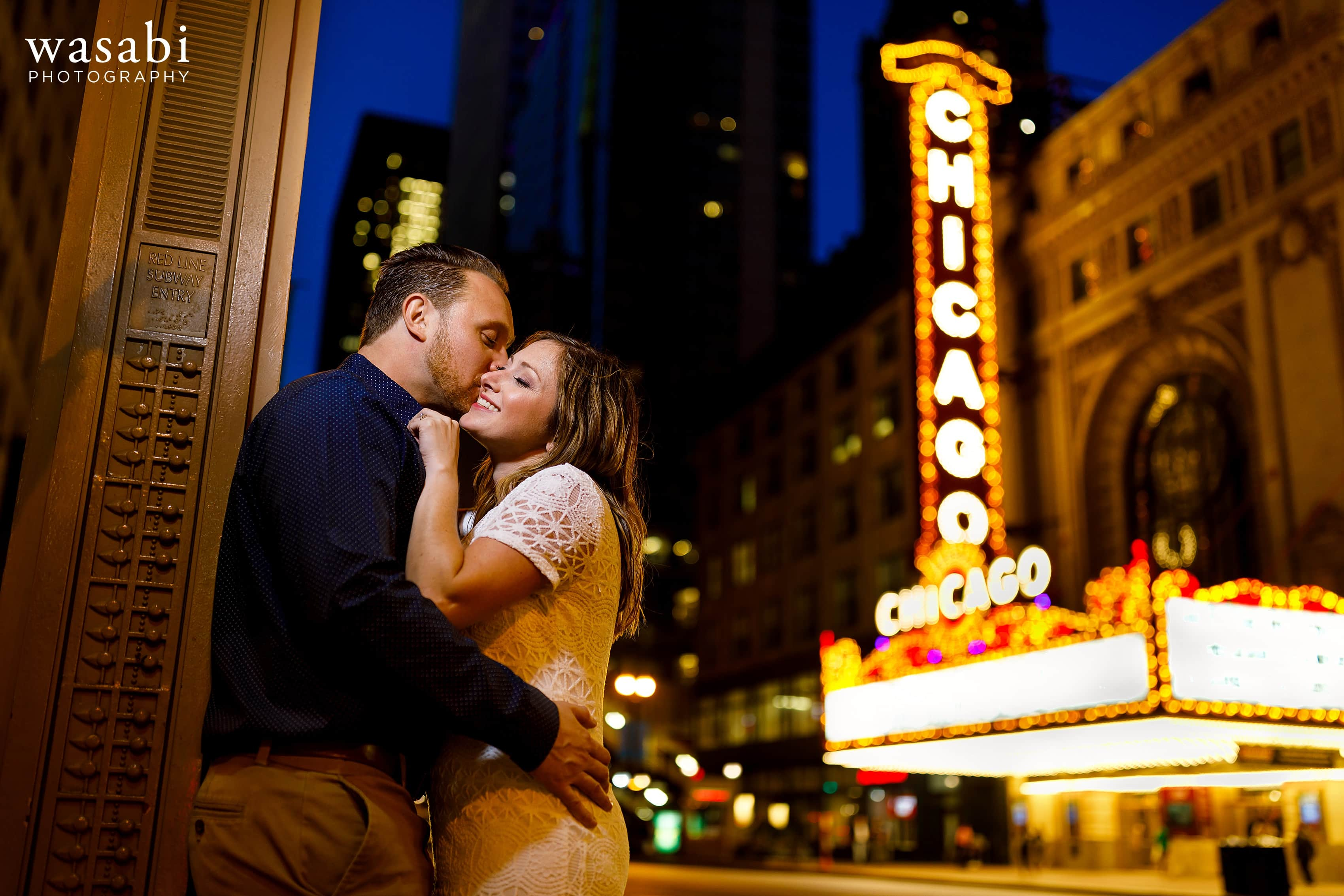 Couple poses at Red Line entrance in front of the iconic Chicago Theatre sign on State Street in Chicago
