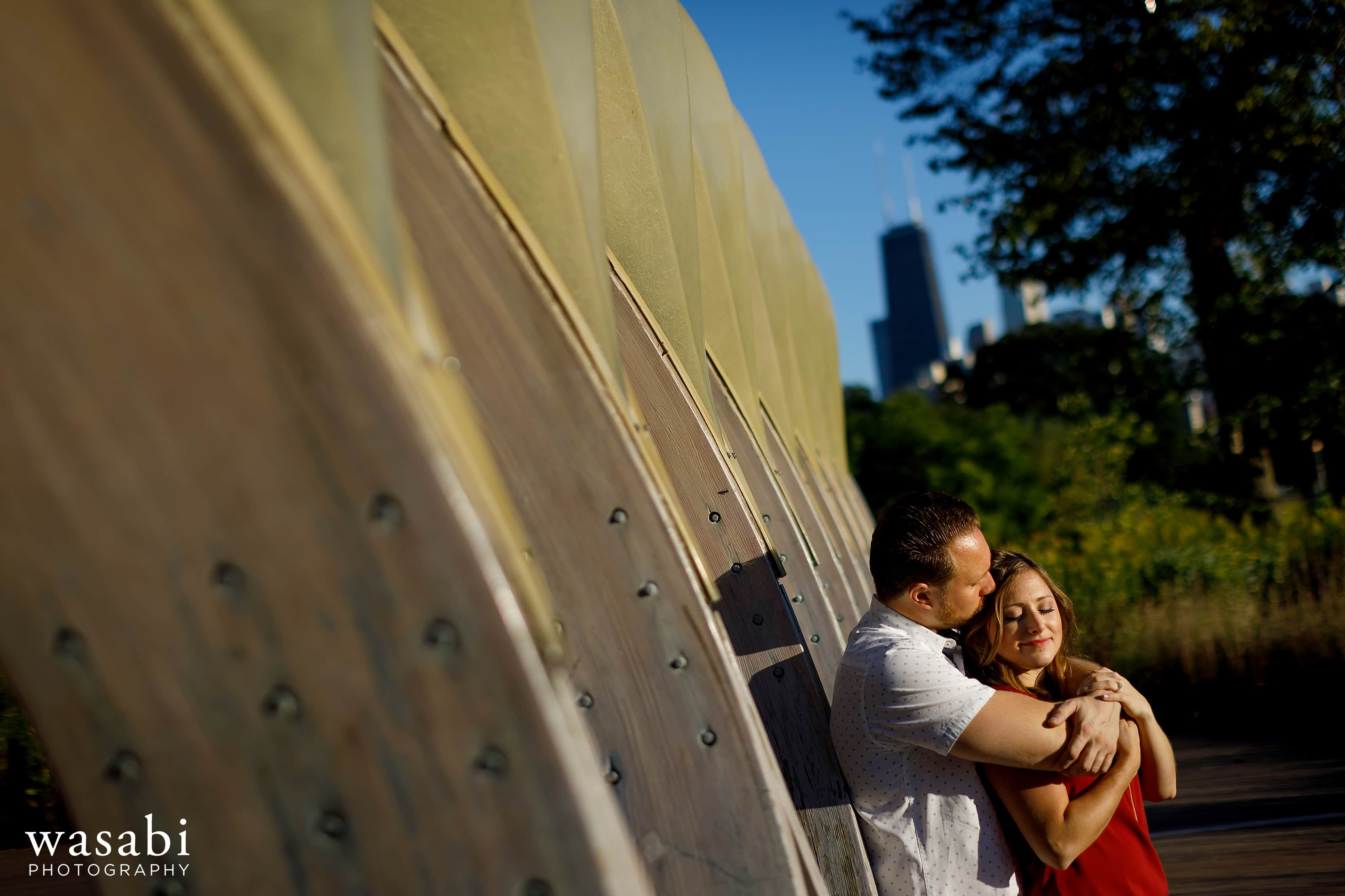 Couple poses for engagement photos at Lincoln Park honeycomb wood arch Peoples Gas Education Pavilion during their engagement session in Chicago