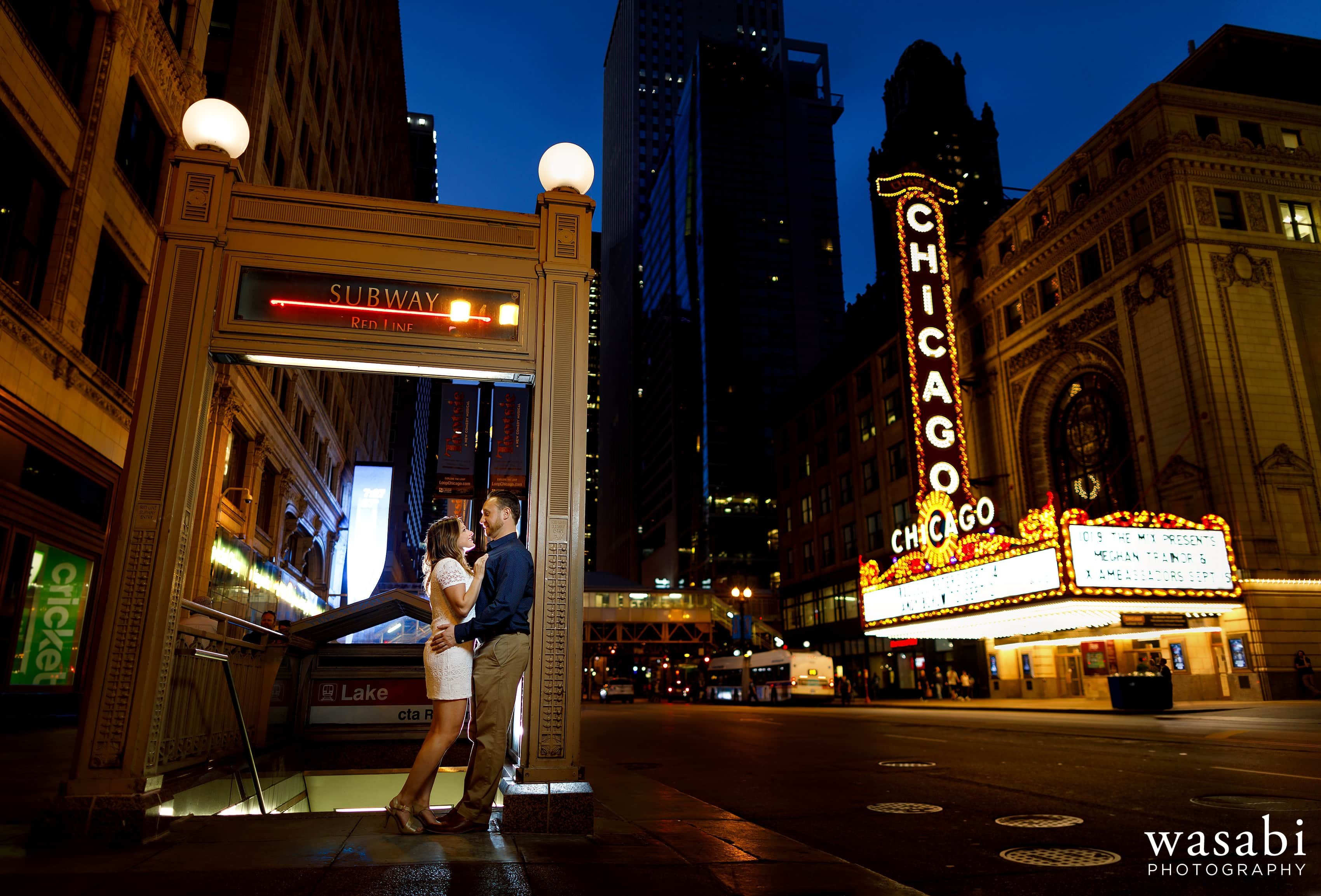 Couple poses under Red Line entrance in front of the iconic Chicago Theatre sign on State Street in Chicago