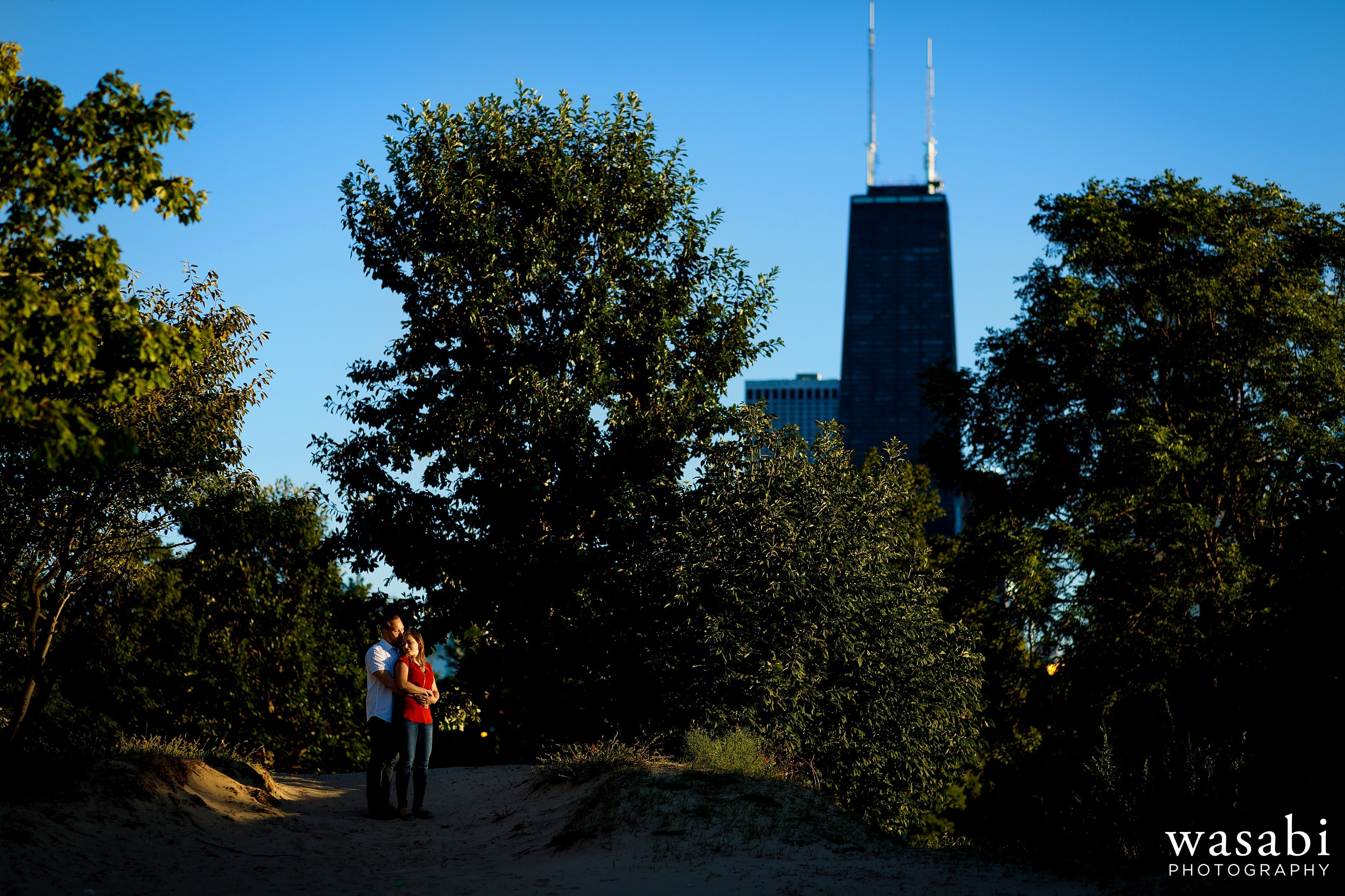 Couple walks along Lake Michigan beach lakeshore during engagement photos at North Ave. Beach