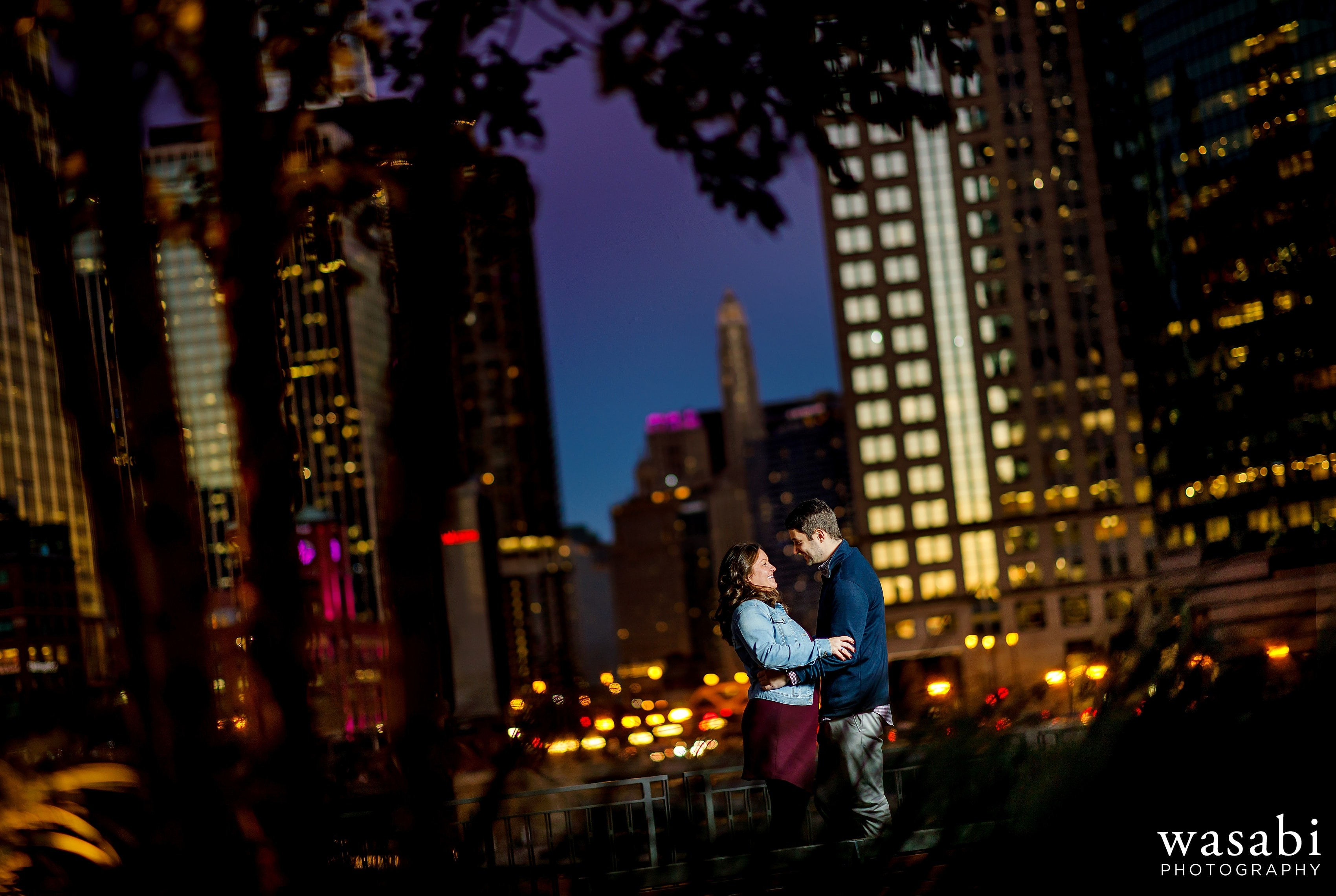 Couple poses for engagement photos at Gibsons Italia with Chicago Skyline in the background