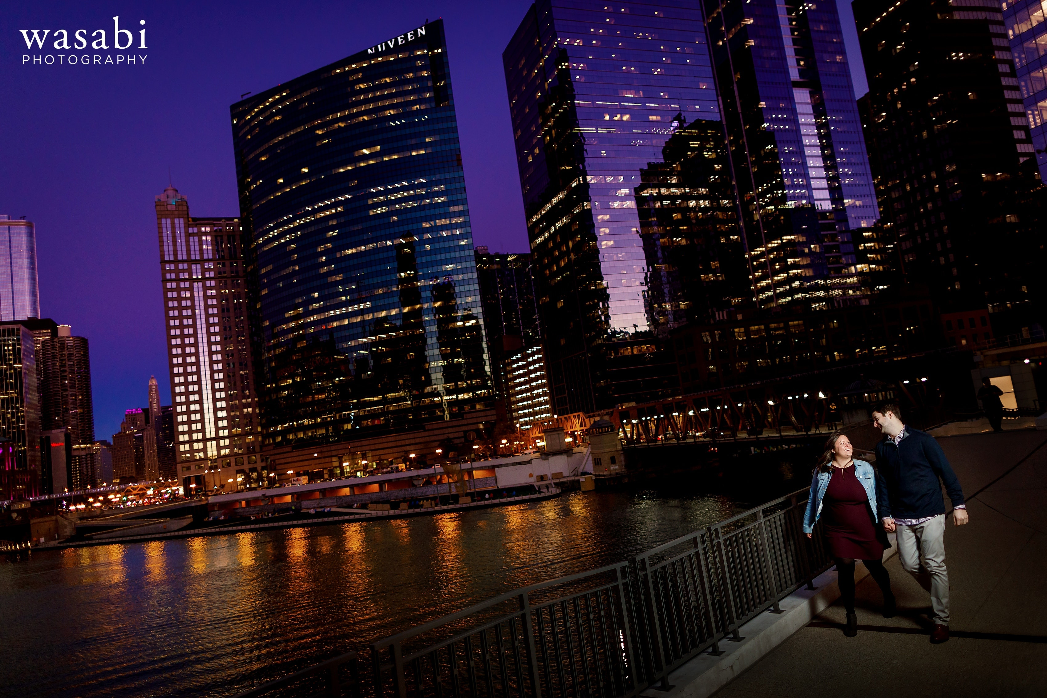 Couple walks along Chicago River during a colorful Chicago engagement session at Gibsons Italia with Chicago Skyline in the background