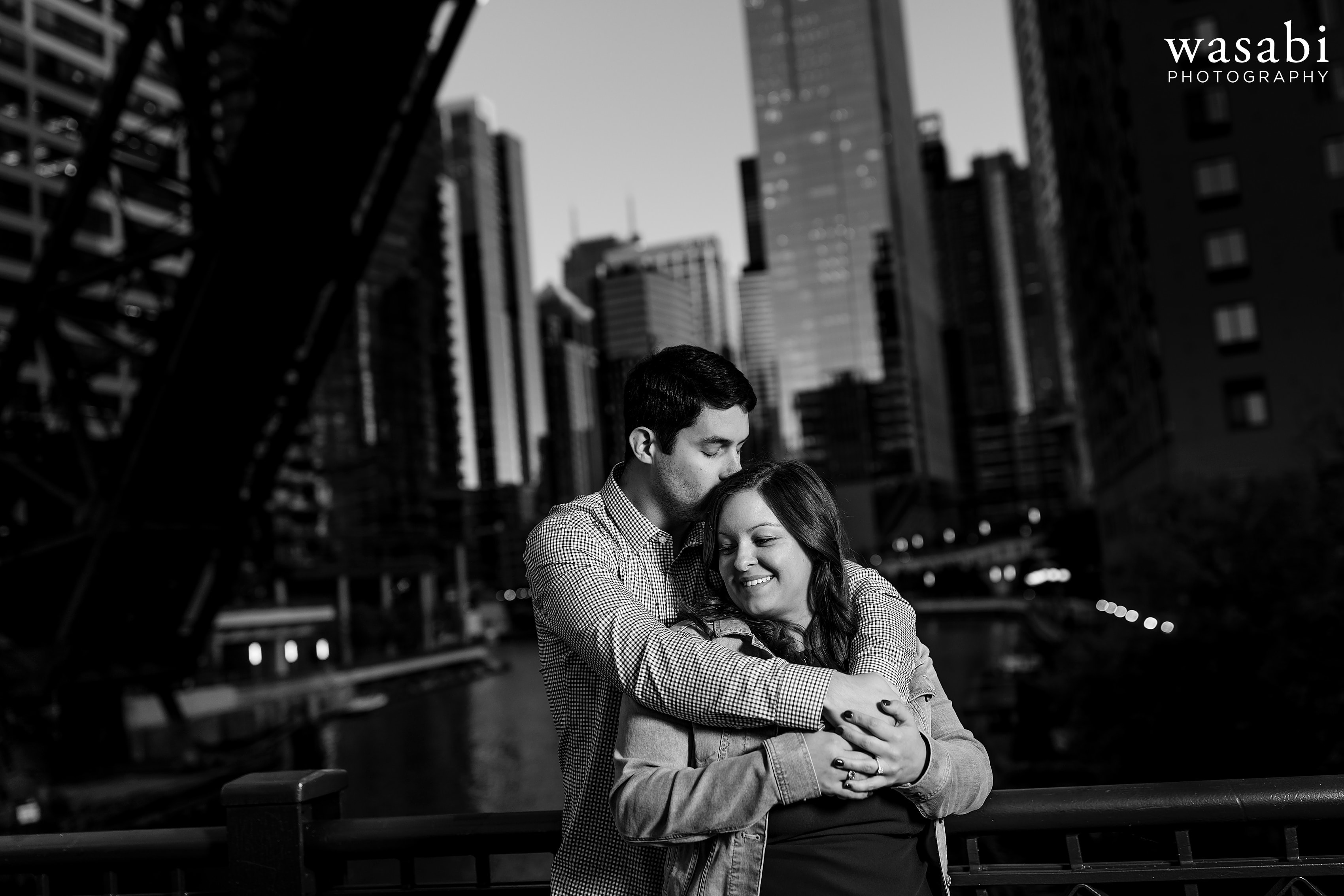 couple kisses on kinzie street bridge during engagement session in Chicago