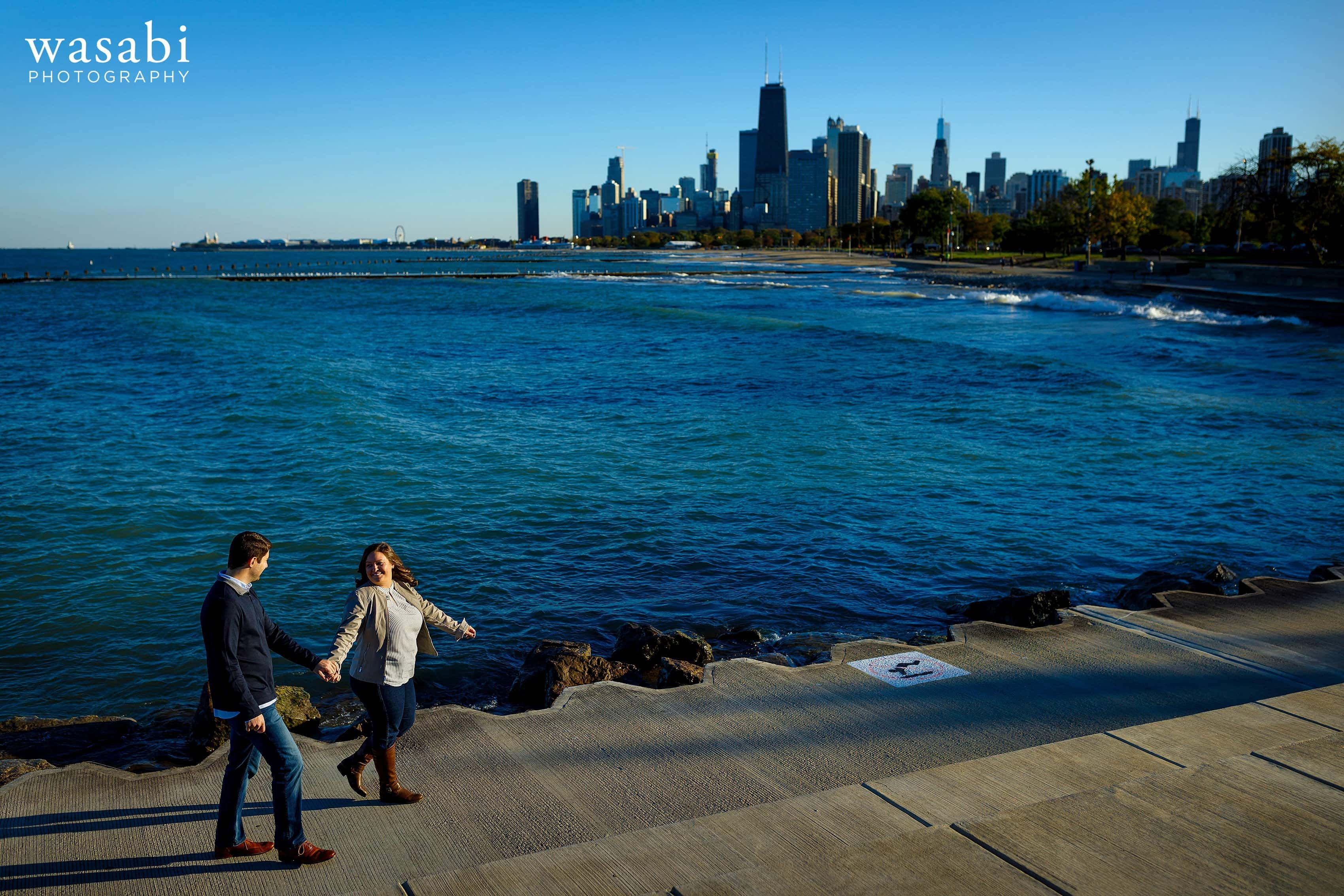 couple walks along the Lake Michigan waterfront with Chicago Skyline in the background at Fullerton Ave. Beach