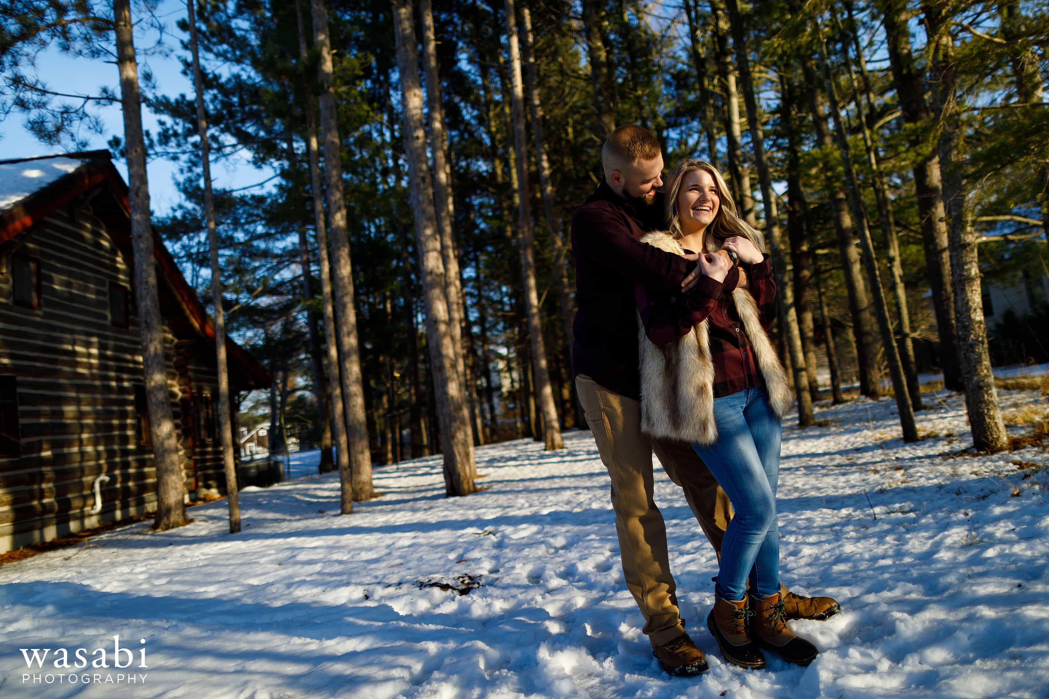 couple poses for engagement photo with coniferous trees in the background during winter engagement session in Glen Arbor Michigan