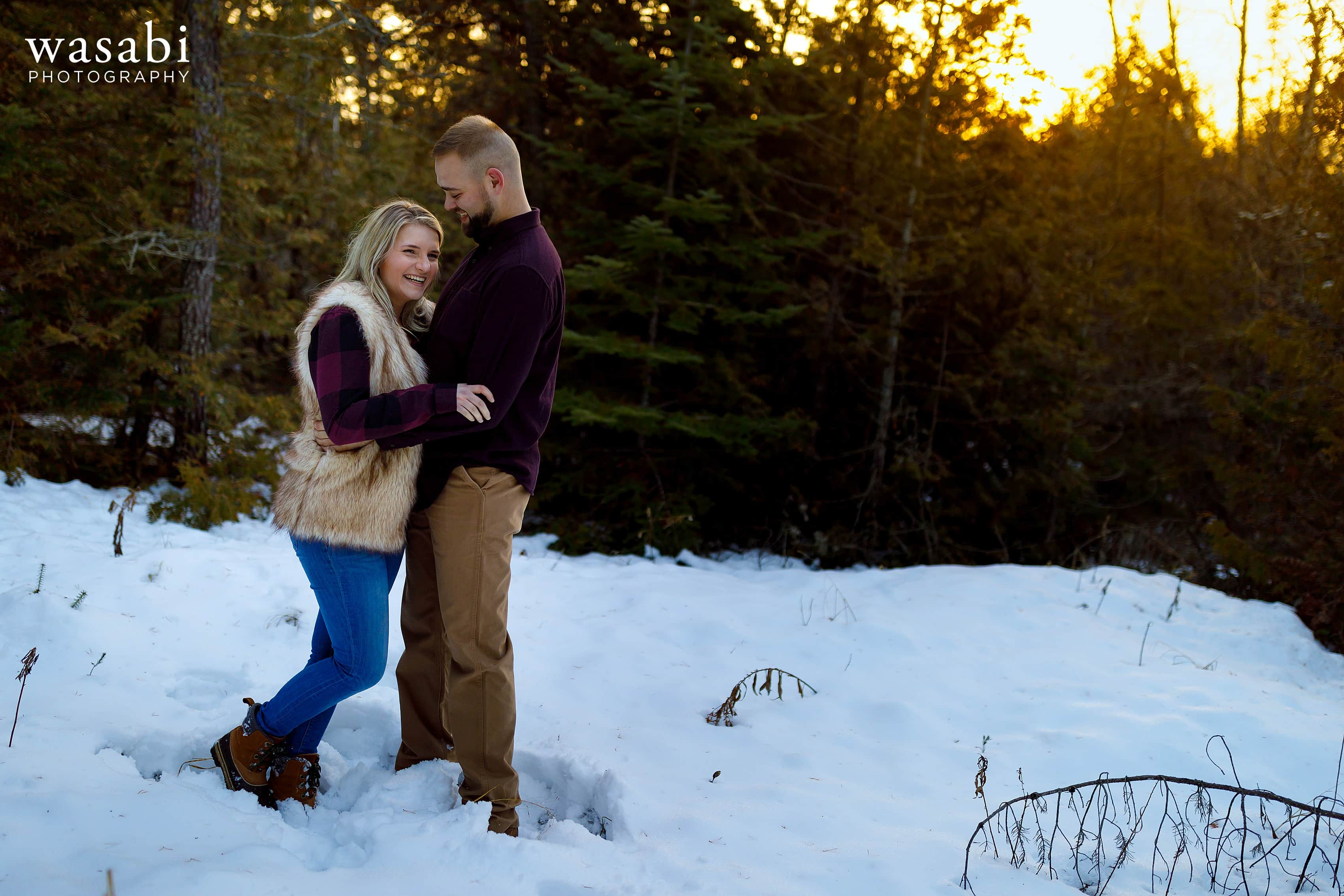 couple poses for engagement photo with pine trees and sunset in the background during winter engagement session in Glen Arbor Michigan
