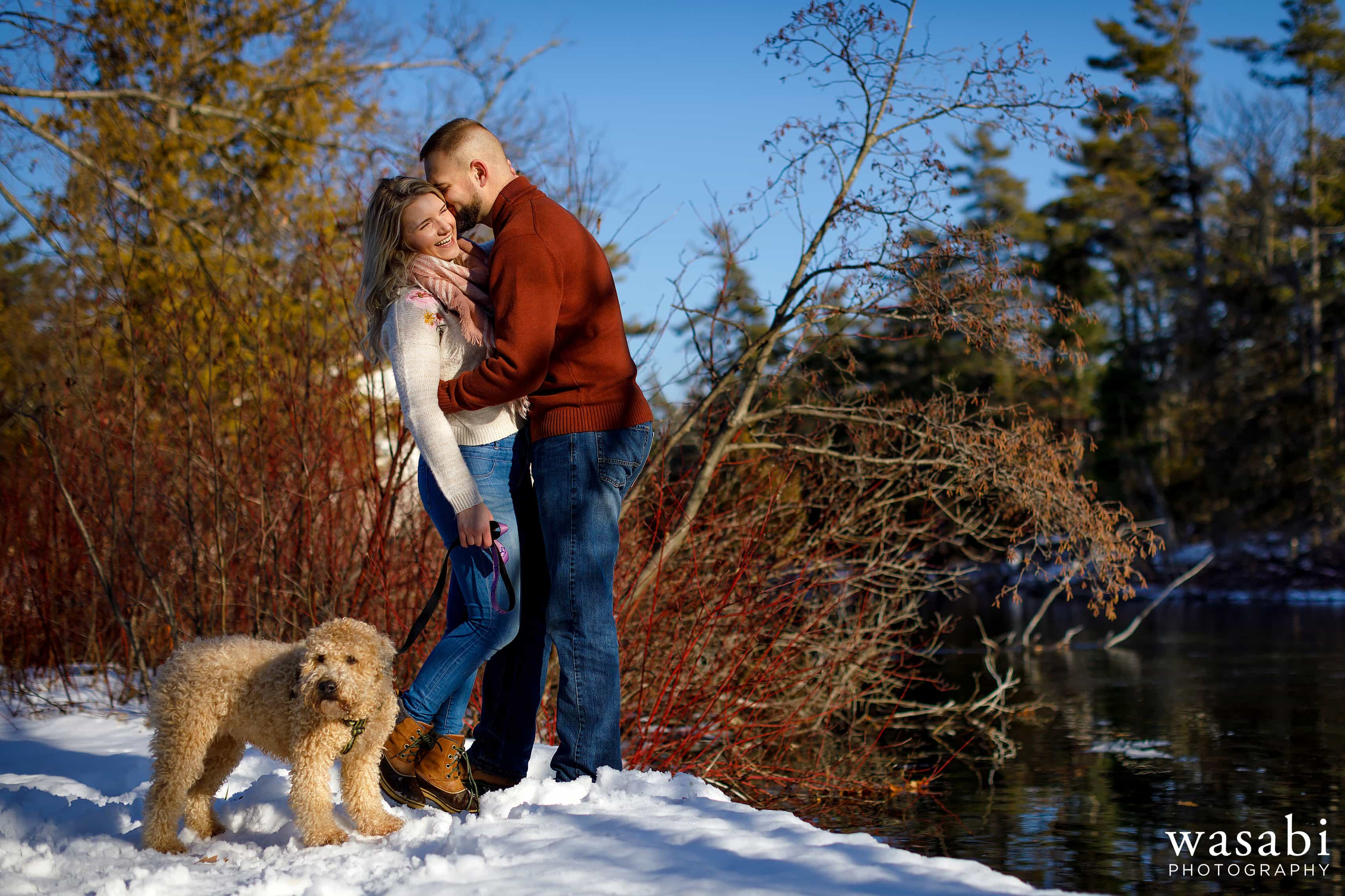 couple poses for engagement photo with their dog along a river during winter engagement session in Glen Arbor Michigan