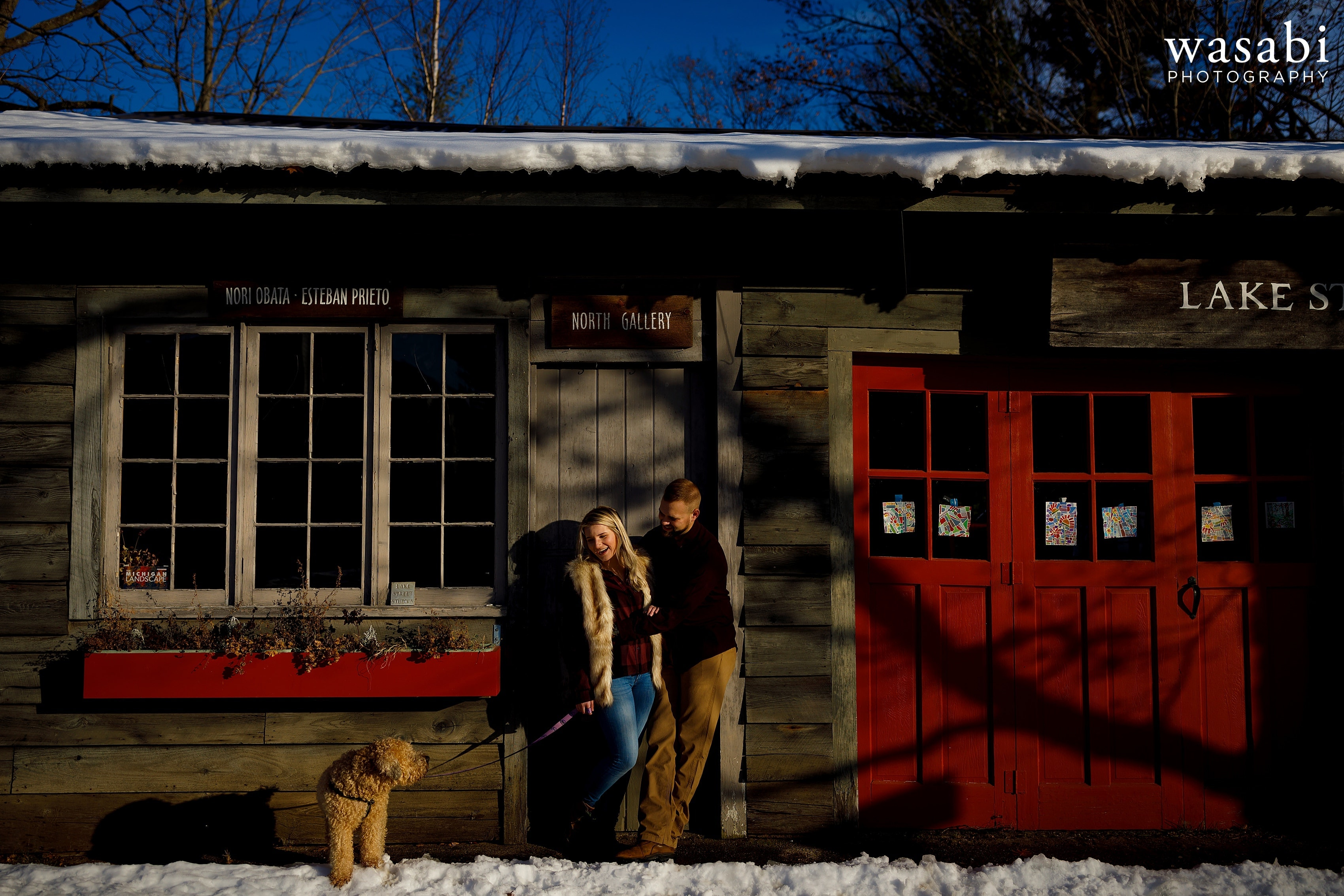 couple poses for engagement photo with their dog in front of barn and red doors during winter engagement session in Glen Arbor Michigan